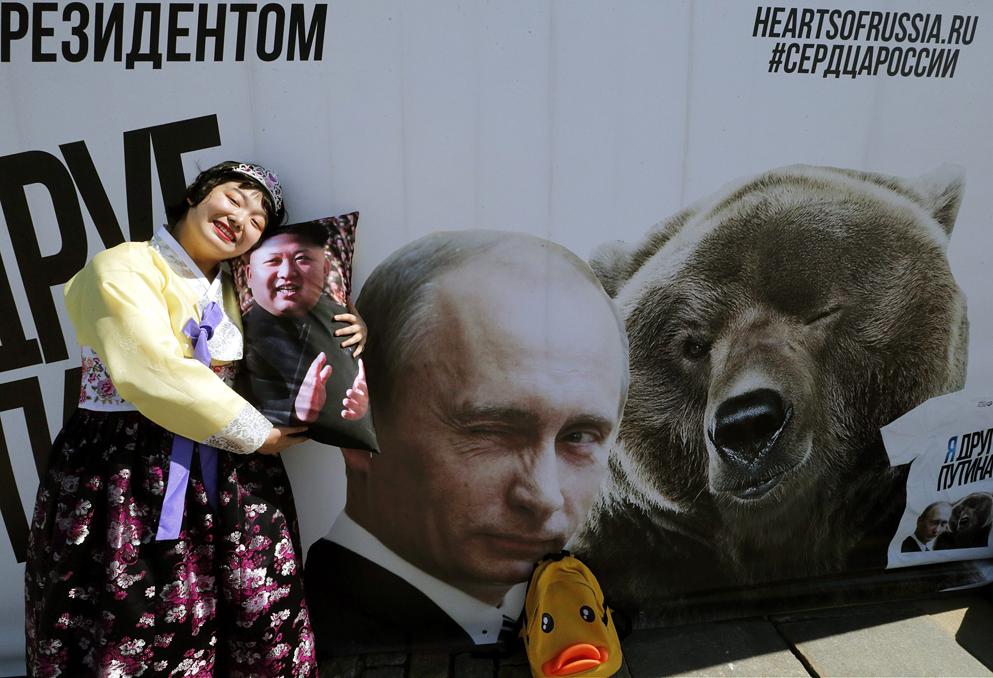 70th anniversary of the end of World War II...epa04738576 North Korean tourist poses with a souvenir pillow decorated with an portrait of Kim Jong-un in front of  a poster showing Vladimir Putin and a bear at the Victory park in Moscow, Russia, 08 May 2015.  On May 09 Russia will celebrate the 70th anniversary of the victory of the Soviet Union and it's Allies over Nazi Germany in WWII.  EPA/ANATOLY MALTSEV