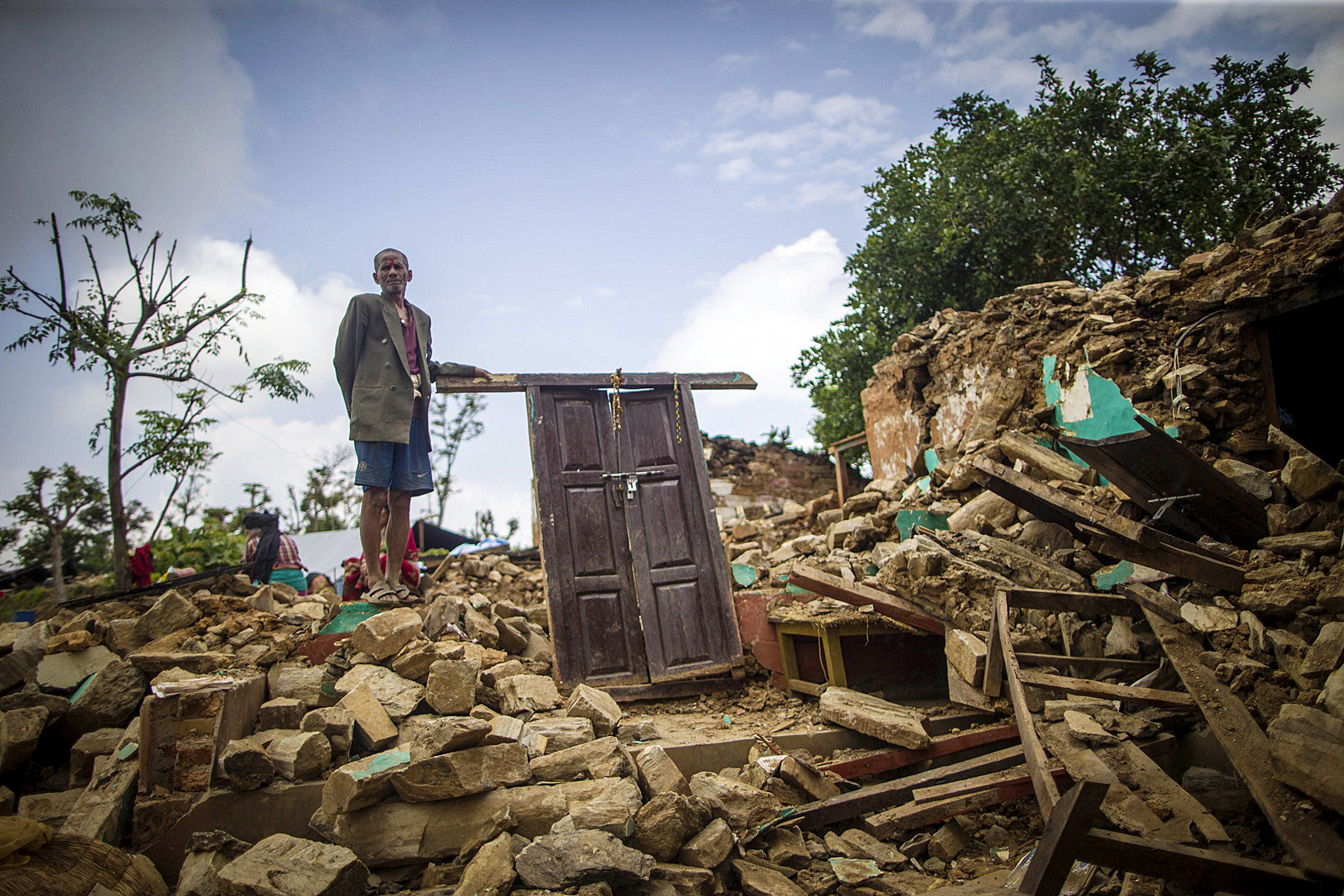 This photo taken on April 30, 2015 shows...This photo taken on April 30, 2015 shows an elderly man posing for a photo on the ruins of his damaged home in Paslang village in Gorkha, Nepal. Desperate survivors living at ground zero of Nepal's earthquake felt abandoned to their fate on May 1 after losing their loved ones and livelihoods in a disaster that has claimed more than 6,300 lives.     CHINA OUT   AFP PHOTOSTR/AFP/Getty Images