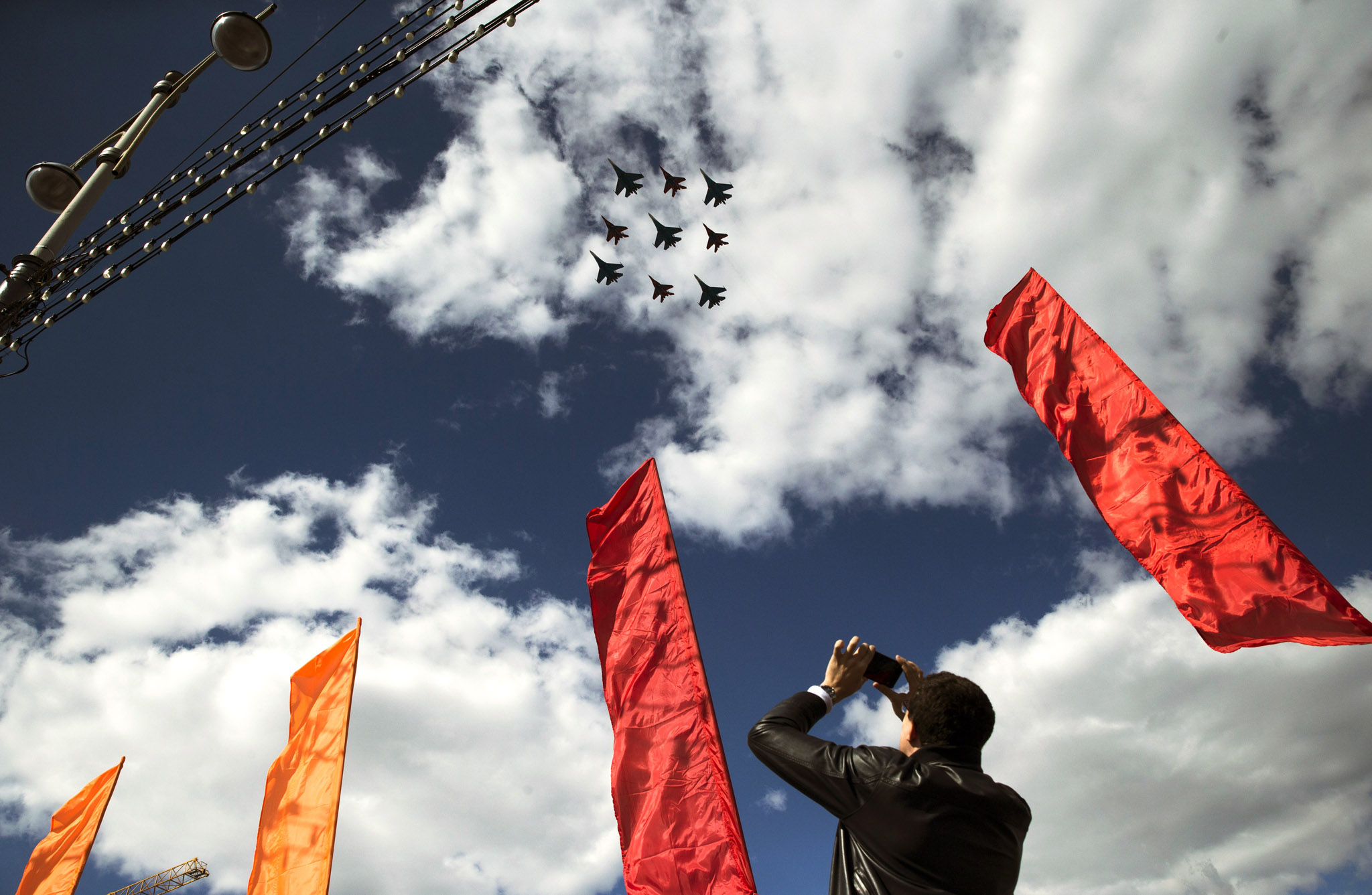 A man takes a picture of Russian Air Force fighter jets as they fly over Moscow during a rehearsal for the Victory Day military parade which will take place at Moscow's Red Square on May 9, in Moscow, Russia, Tuesday, May 5, 2015. (AP Photo/Pavel Golovkin)