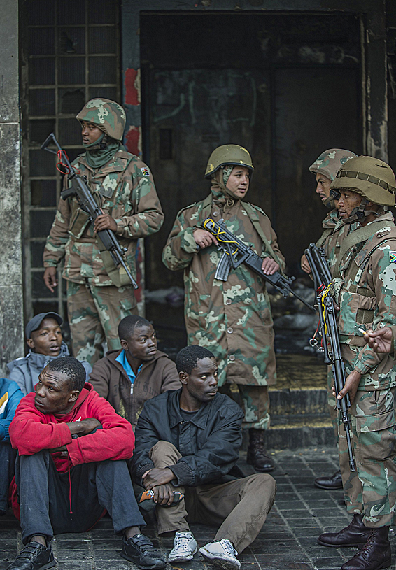 South African Police officers and soldie...South African Police officers and soldiers from the South African Defence Force SADF guard migrants sitting after raiding buildings in Johannesburg central business district in the early hours of the morning on May 8, 2015 in an operation where more than 300 illegal immigrants and foreign nationals were arrested. AFP PHOTO / MUJAHID SAFODIENMUJAHID SAFODIEN/AFP/Getty Images