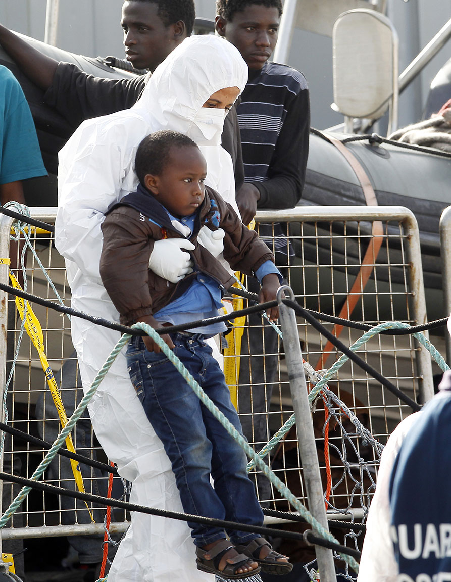 A worker in sanitary outfit holds a boy as migrants disembark from the Iceland Coast Guard vessel Tyr, at the Messina harbor, Sicily, southern Italy, Wednesday, May 6, 2015. This weekend saw a dramatic increase in rescues as smugglers in Libya took advantage of calm seas and warm weather to send thousands of would-be refugees out into the Mediterranean in overloaded rubber boats and fishing vessels. (AP Photo/Antonio Calanni)