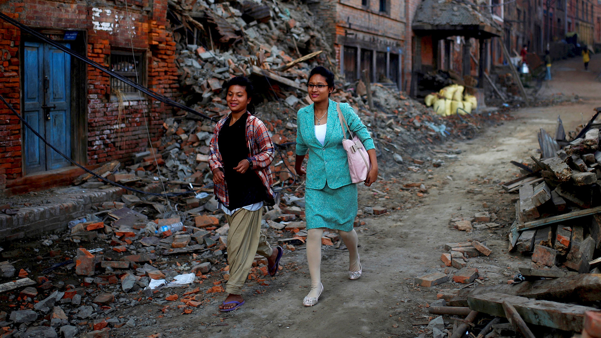 Women walk through debris in the early morning hours in Bhaktapur