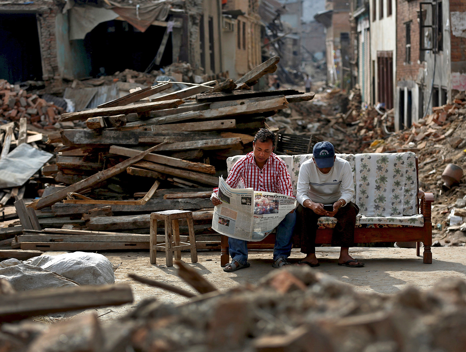 A man reads a newspaper as his friend looks at his mobile phone, as they sit next to collapsed houses on the outskirts of in Kathmandu