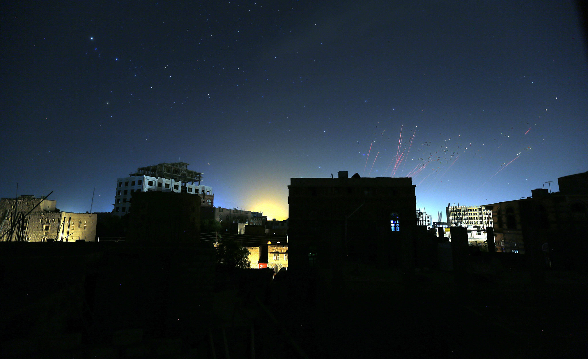 Saudi-led military coalition against Yemen's Houthi rebels...epa04745670 The sky over Sana'a is illuminated by anti-aircraft fire during an alleged airstrike of the Saudi-led coalition ahead of a 5-day ceasefire in Sana'a, Yemen, late 12 May 2015. A Saudi-led coalition halted its air raids on rebel-held positions in neighbouring Yemen late Tuesday as a 5-day ceasefire went into effect at 11 pm local time (2000 GMT). The ceasefire, which is intended to allow badly-needed humanitarian aid reach people affected by the conflict, was preceded by a day of intensive airstrikes on positions held by the Houthi rebels in northern and central Yemen.  EPA/YAHYA ARHAB