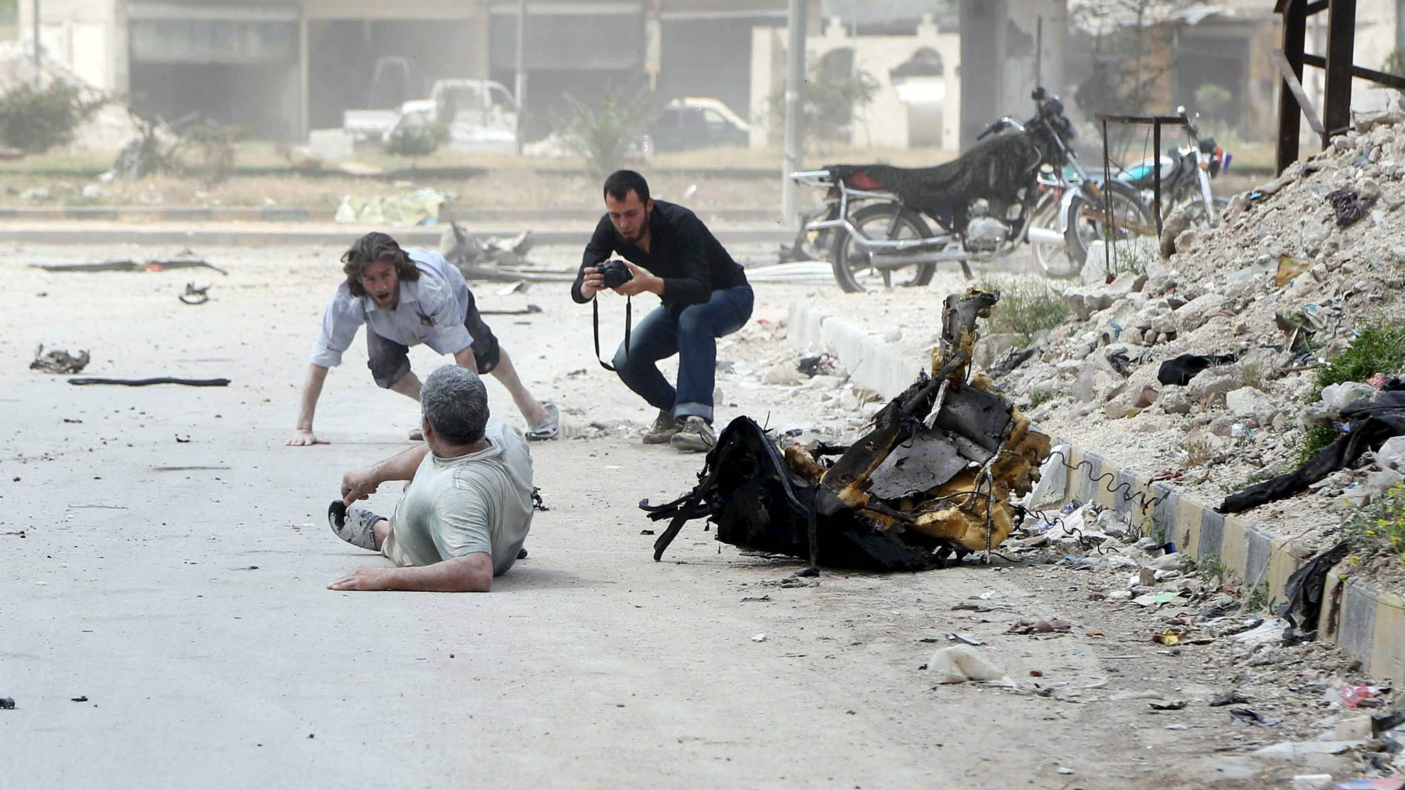 A man takes pictures of civilians lying down to take cover after hearing what activists said was shelling by forces loyal to Syria's President Bashar al-Assad in Jisr al-Hajj roundabout in Aleppo