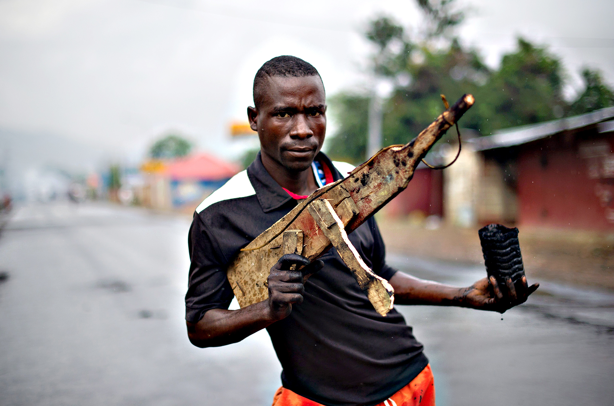 A man poses with a wooden rifle in the Musaga neighbourhood in Bujumbura, Burundi on May 5, 2015. Burundi, where a 13-year civil war between Tutsis and Hutus ended only in 2006, has been rocked by violent protests since the ruling party designated President Pierre Nkurunziza to run in elections for a third term, in apparent defiance of the constitution and the Arusha accords which ended the war.