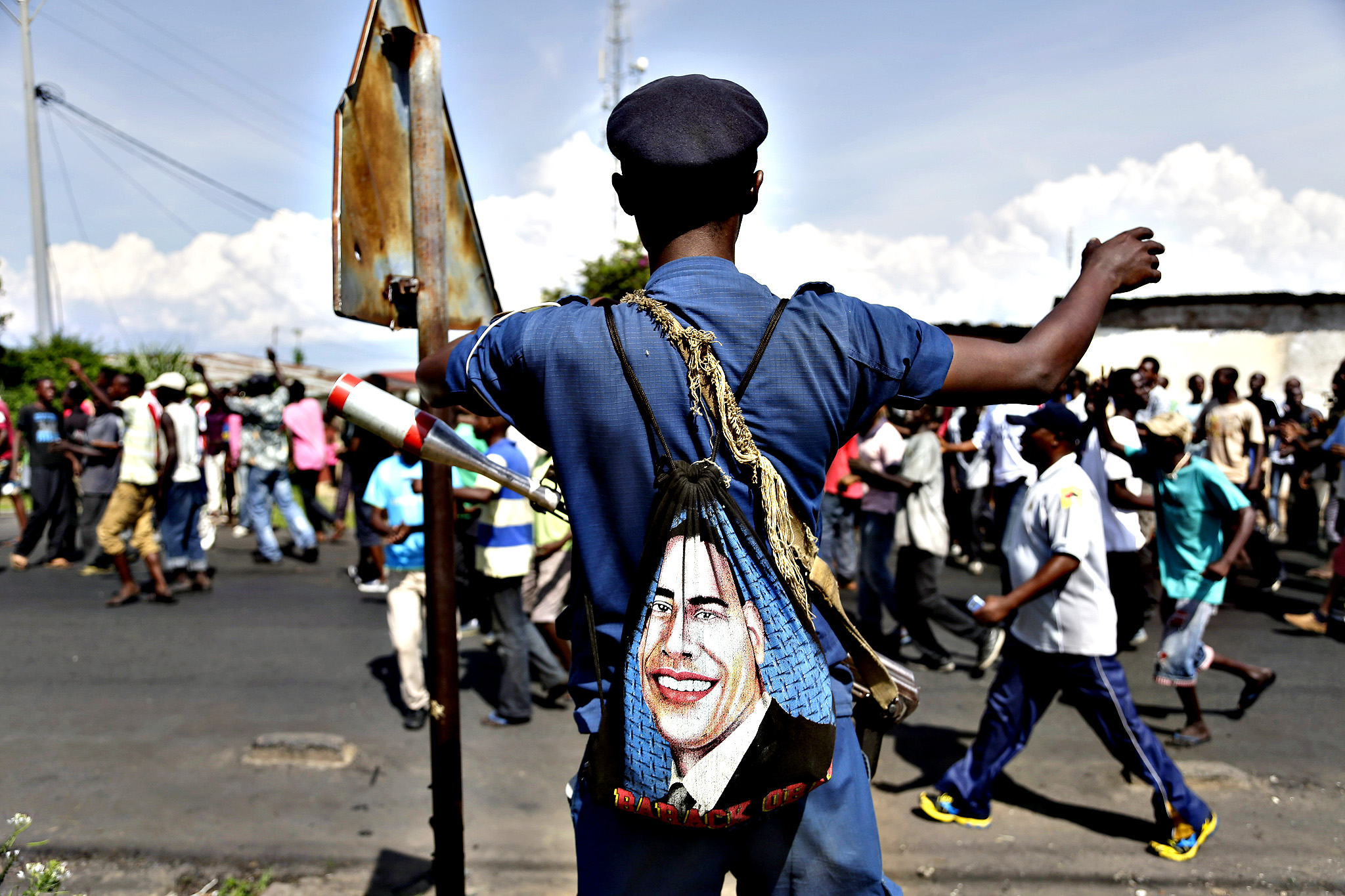 A police officer with a bag depicted the image of US President Barack Obama, stands on patrol as protesters march through the Musaga district of Bujumbura, in Burundi, Monday, May 11, 2015.  Police and army negotiated with over 2000 protesters to allow delivery trucks to enter the city. One person was killed in a clash with Burundi's police on Sunday in demonstrations in the capital, Bujumbura, as the government ordered a ban on any further street protests over President Pierre Nkurunziza's bid for a third term in power.