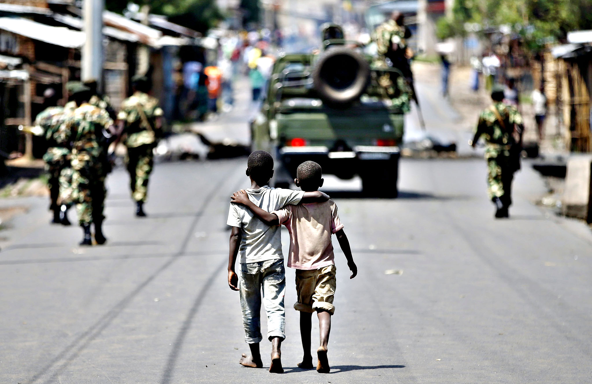 Boys walk behind patrolling soldiers in Bujumbura, Burundi, May 15, 2015. Burundian forces arrested the leader of a failed coup on Friday and President Pierre Nkurunziza returned to the capital, his spokesman said, but protesters pledged to go back to the streets, setting the stage for more clashes.
