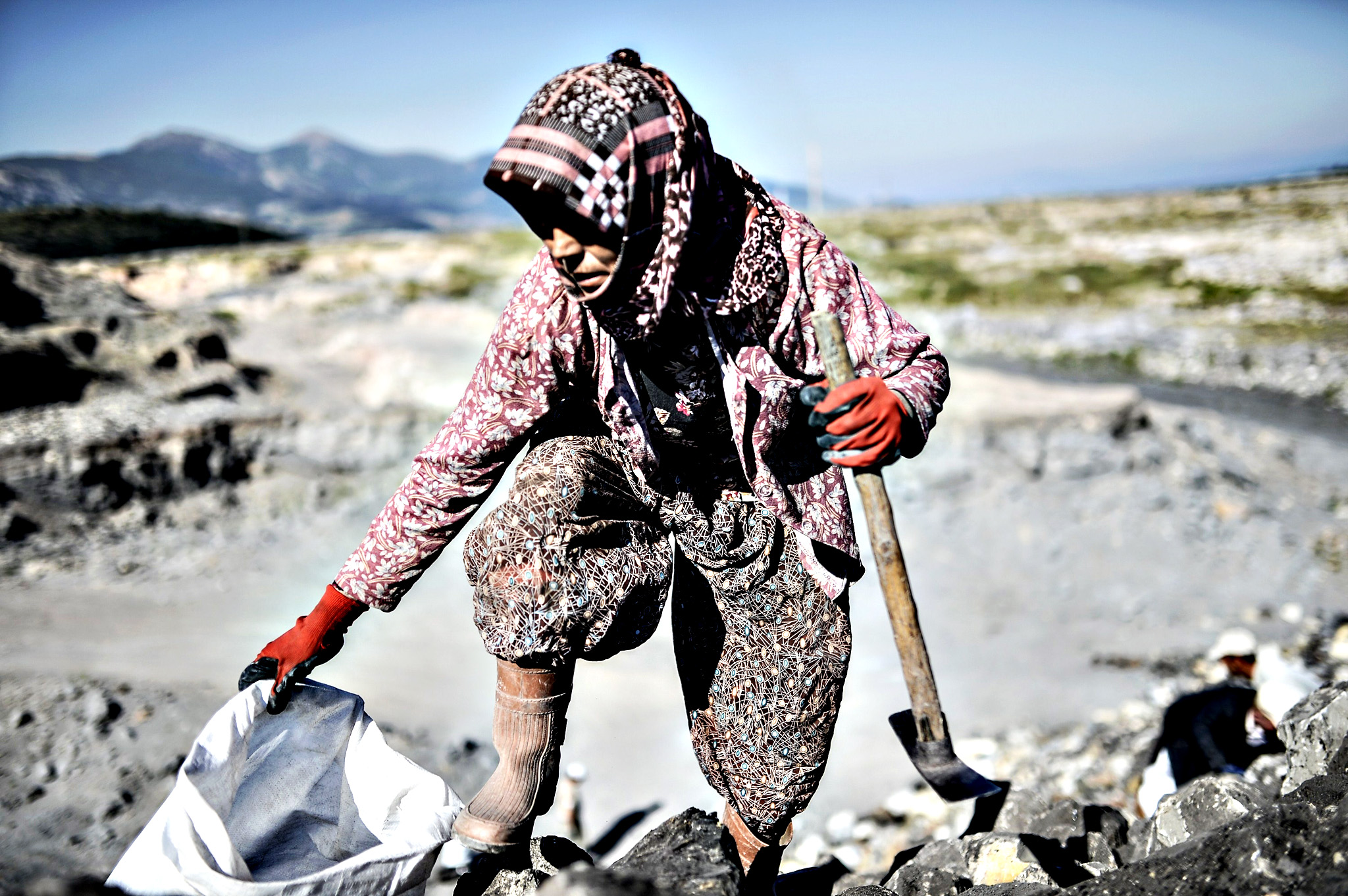 A villager from Yirca collects coal on Monday outside the Soma mine in Manisa. People gathered for the anniversary of the death of 301 workers after an explosion on May 13, 2014.