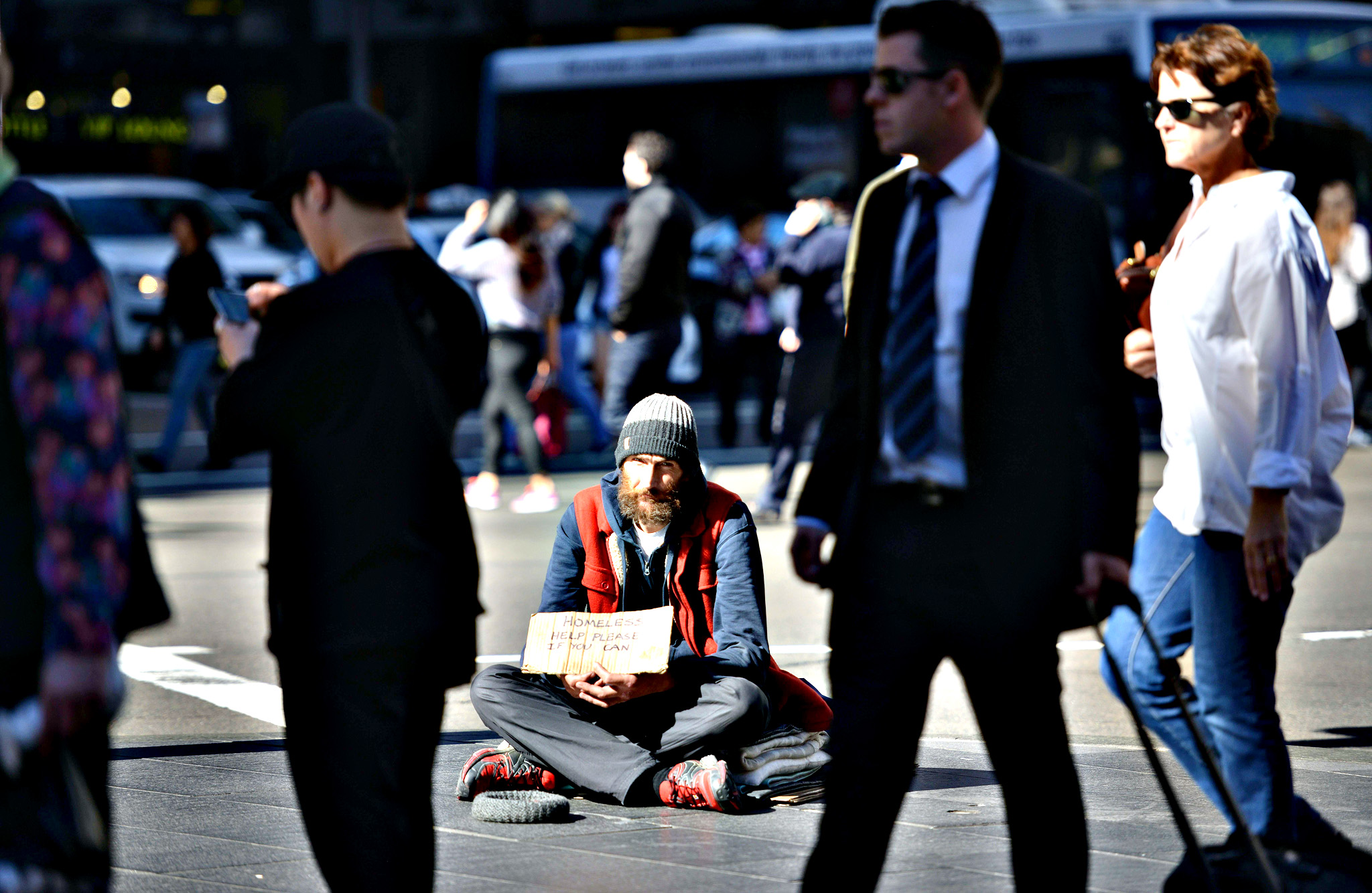 "A homeless man sits on a street in the Central Business District of Sydney as the Australian government prepares to release its 2015/16 budget on Tuesday. Australian Treasurer Joe Hockey insisted he will deliver a ""responsible and fair"" budget as the government battles to juggle slumping revenue and a huge deficit while avoiding a voter backlash"