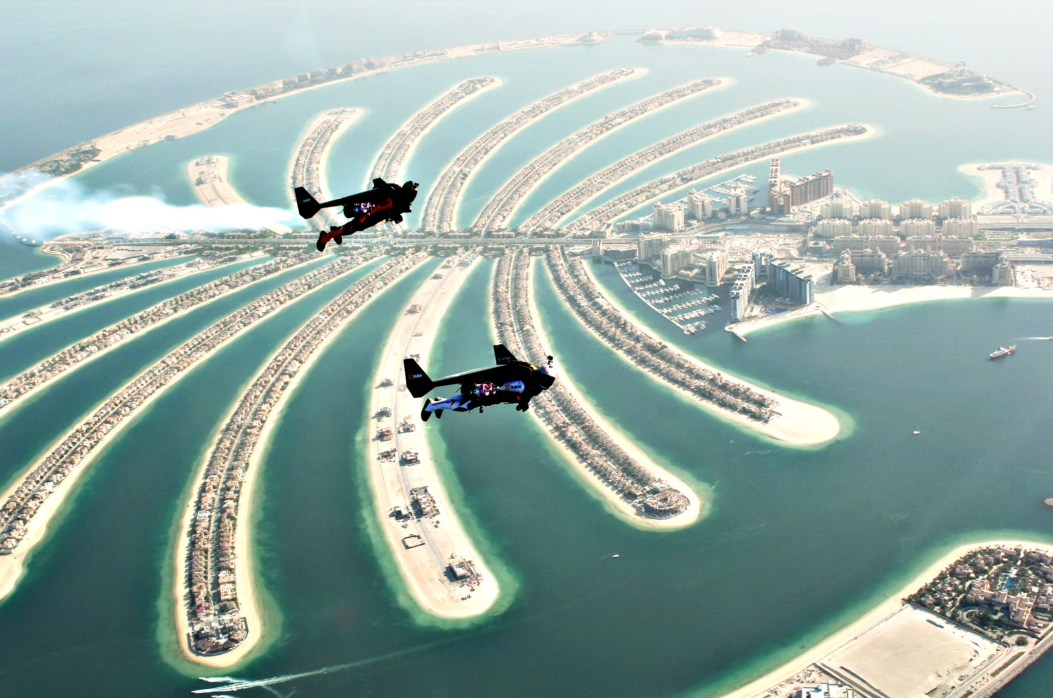 An aerial view taken from a sea plane shows Swiss pilot and original Jetman Yves Rossy and Vince Reffett flying over Dubai's Palm Island...An aerial view taken from a sea plane shows Swiss pilot and original Jetman Yves Rossy (front) and Vince Reffett flying over Dubai's Palm Island, Dubai, United Arab Emirates May 12, 2015