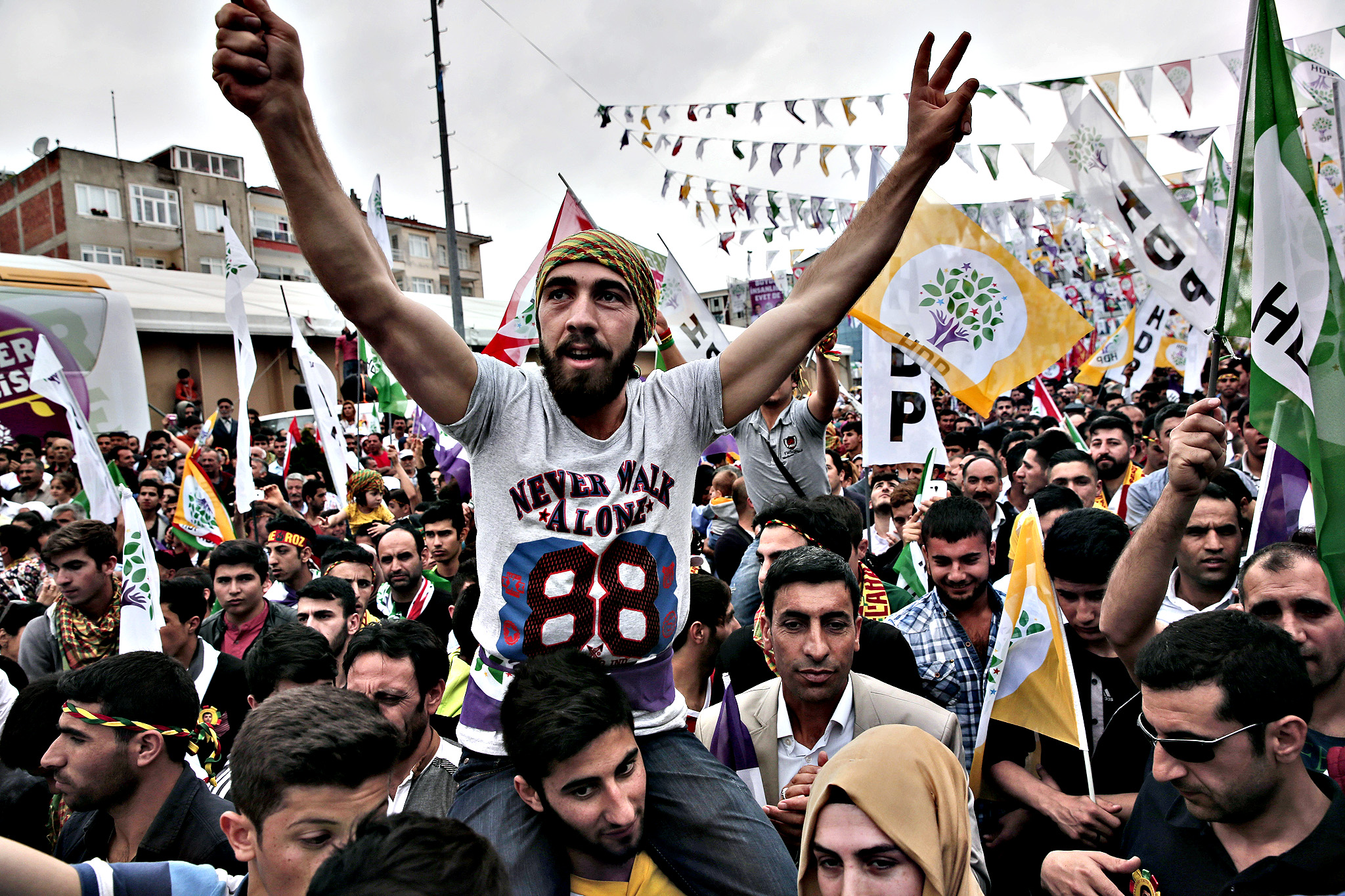 Supporters of the pro-Kurdish People's Democratic Party (HDP) wait for the appearance Selahattin Demirtas, co-chair of the party to deliver an election campaign speech during a rally in Istanbul, Turkey, Thursday, May 21, 2015, before Turkey's general election on June 7.  The ADP is a small party, but if it gains 10 percent of the vote it will enter parliament as a party, and could change the face of the country's politics