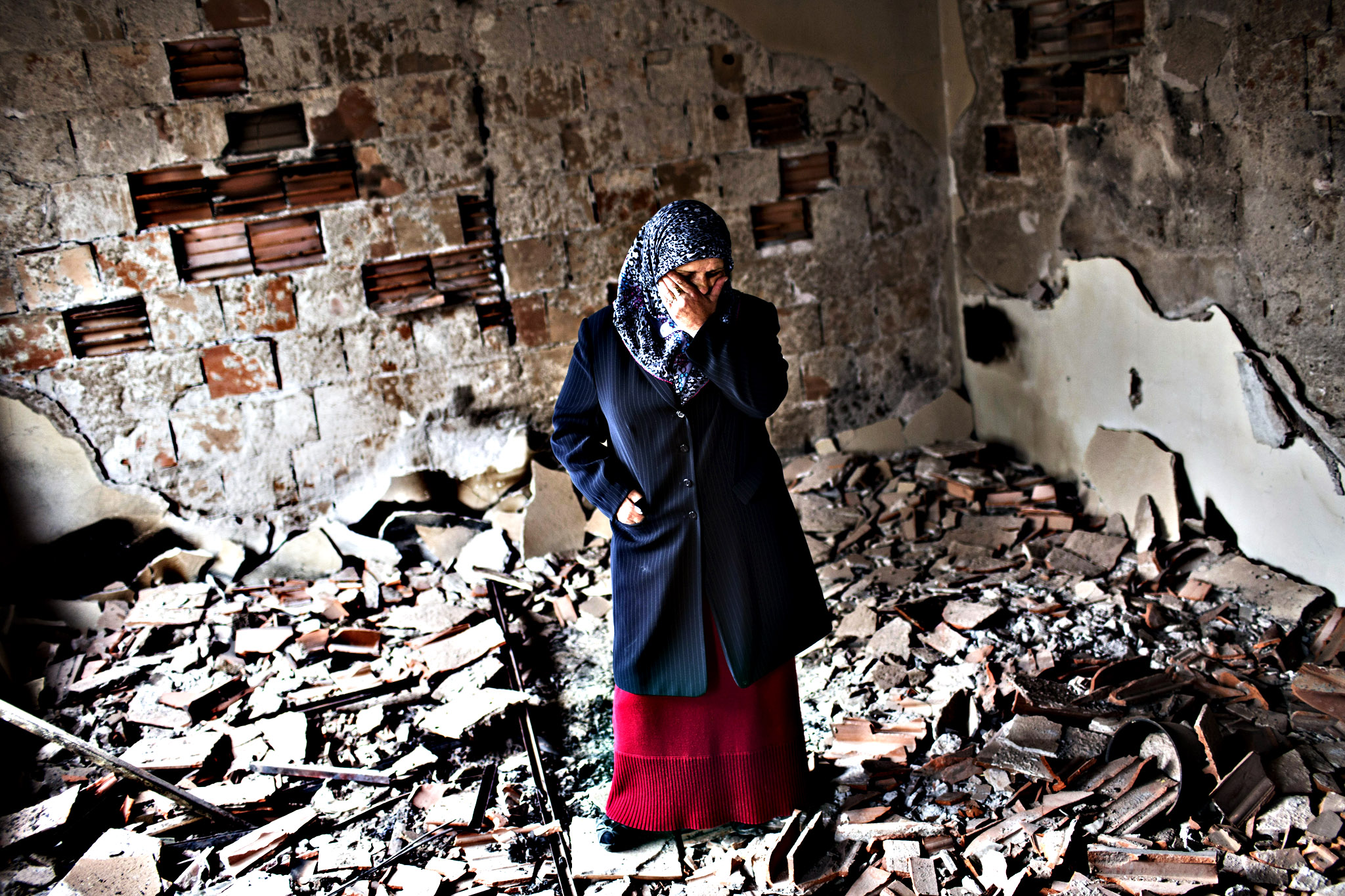 Habibe Biyali stands inside a room in her house heavily damaged by fighting in Kumanovo, Macedonia, Monday, May 11, 2015.  Residents are returning to their homes in a northern Macedonian town where a fierce weekend battle between special police units and alleged ethnic Albanian militants left 22 dead and at least 37 injured
