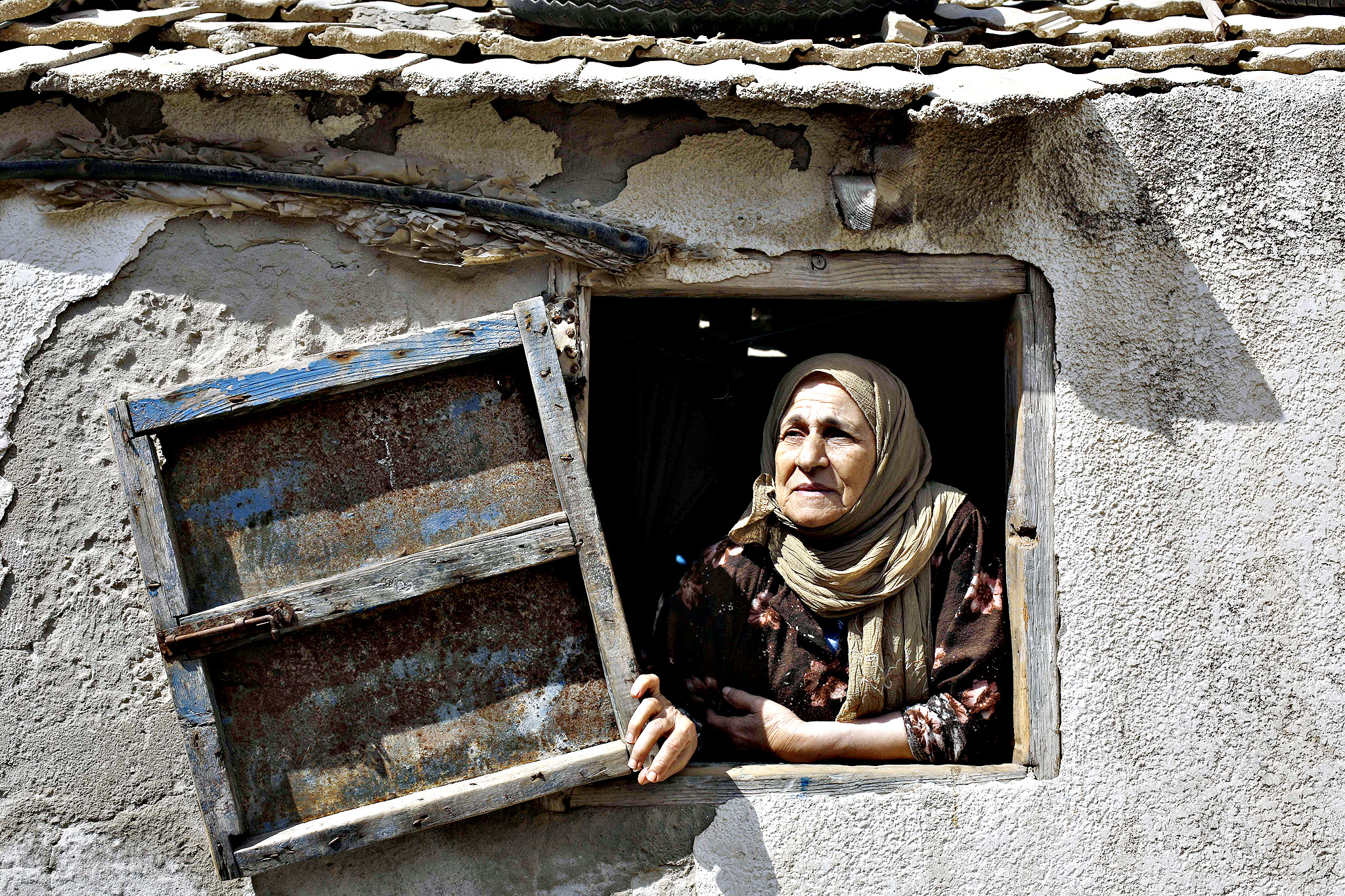 "A Palestinian woman looks from a window of her house in the Al-Shati refugee camp in Gaza City on May 14, 2015 ahead of the commemorations for the 67th anniversary of the ""Nakba"". ""Nakba"" means in Arabic ""catastrophe"" in reference to the birth of the state of Israel 67-years-ago in British-mandate Palestine, which led to the displacement of hundreds of thousands of Palestinians who either fled or were driven out of their homes during the 1948 war over Israel's creation"