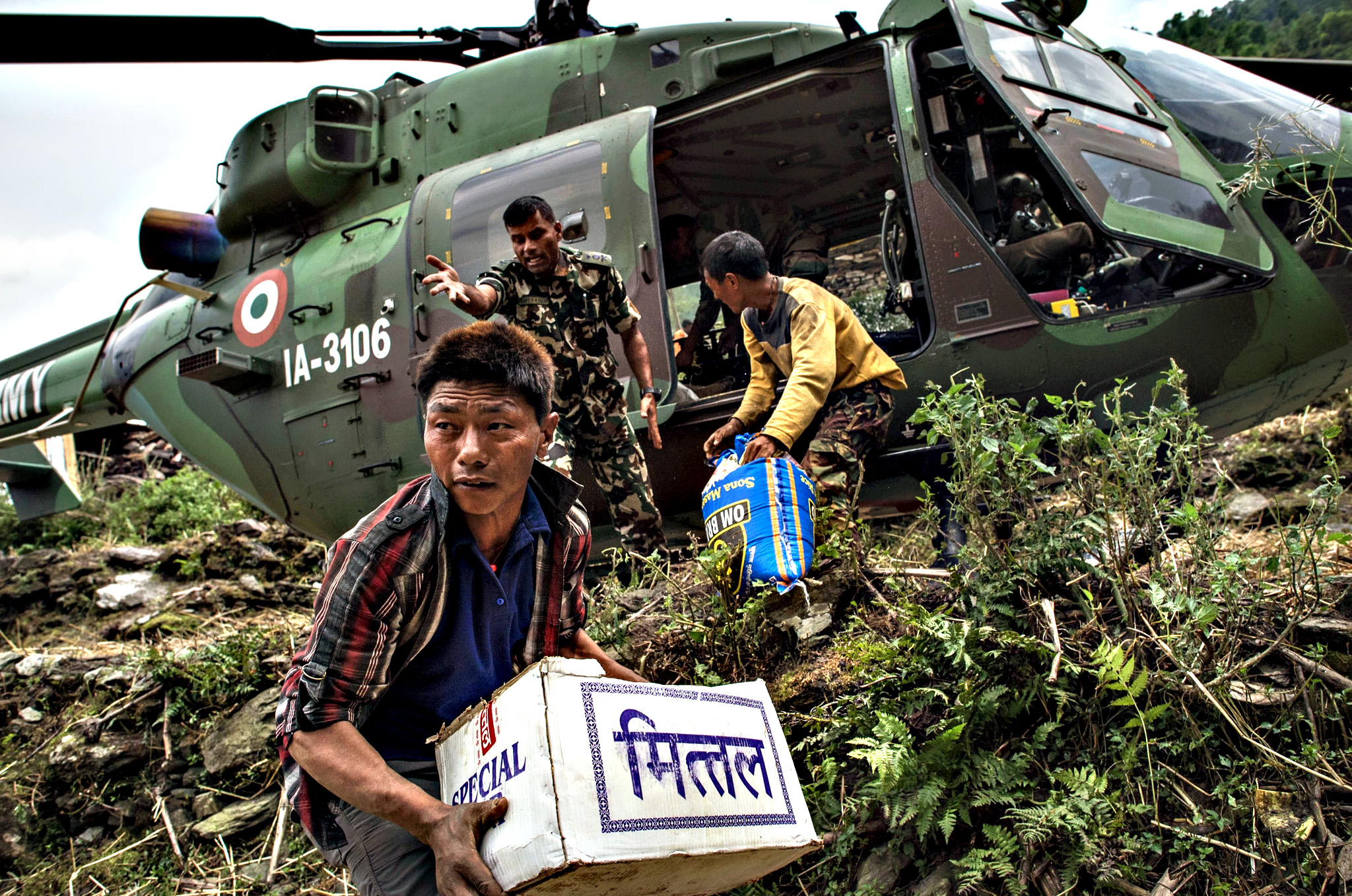 Nepalese villagers collect aid dropped by an Indian helicopter on Wednesday in Hulchuk, Nepal.  A major 7.9 earthquake hit Kathmandu mid-day on Saturday 25th April, and was followed by multiple aftershocks that triggered avalanches on Mt. Everest that buried mountain climbers in their base camps. Many houses, buildings and temples in the capital were destroyed during the earthquake, leaving over 7000 dead and many more trapped under the debris as emergency rescue workers attempt to clear debris and find survivors. Regular aftershocks have hampered recovery missions as locals, officials and aid workers attempt to recover bodies from the rubble