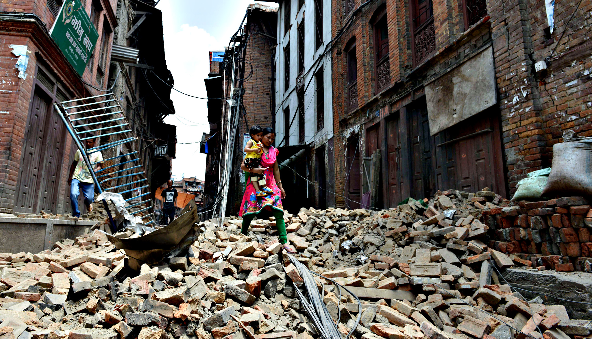 A Nepalese resident carries a child as she walks past damaged homes in Bhaktapur on the outskirts of Kathmandu on May 13, 2015, following a new earthquake that hit May 12.  Rescuers were battling to reach survivors of a deadly new earthquake in Nepal that triggered landslides and brought down buildings, as the search continued for a US military helicopter that went missing while delivering aid. Thousands of traumatised survivors spent the night outdoors, afraid to return to their houses after the 7.3-magnitude quake hit, less than three weeks after the country was devastated by its deadliest quake in more than 80 years.