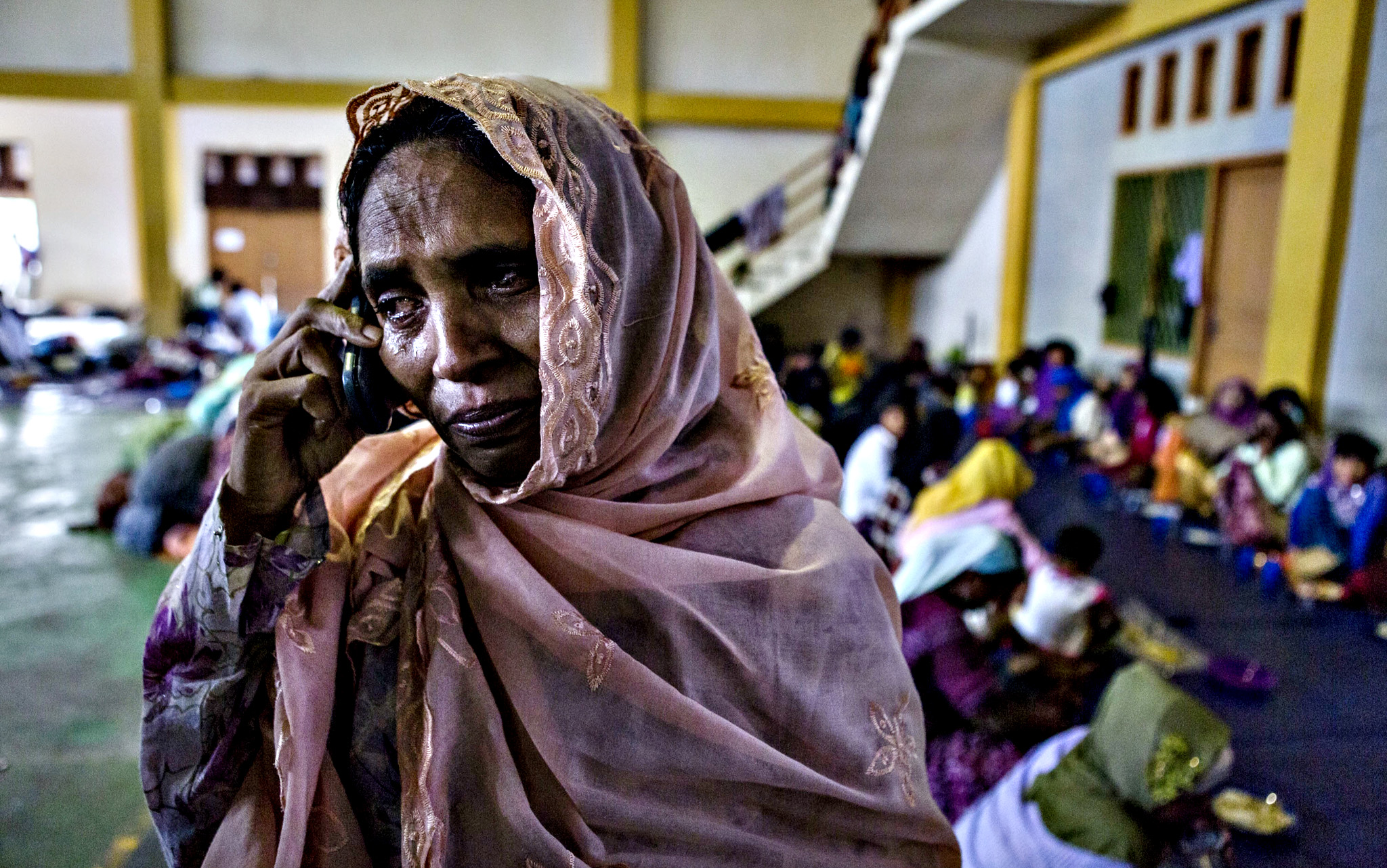 An Rohingya woman, Samsidah Begom binti Abdul Syukur, cries as make a phone call to her son in Malaysia at a shelter on Tuesday in Lhoksukon, Aceh province, Indonesia. Boats carrying over 500 of Myanmar's Rohingya refugees have arrived in Indonesia, many requiring medical attention. They have warned that thousands more are thought to be still at sea. Myanmar's Rohingya Muslim community have long been persecuted and marginalized by Myanmar's mostly Buddhist population