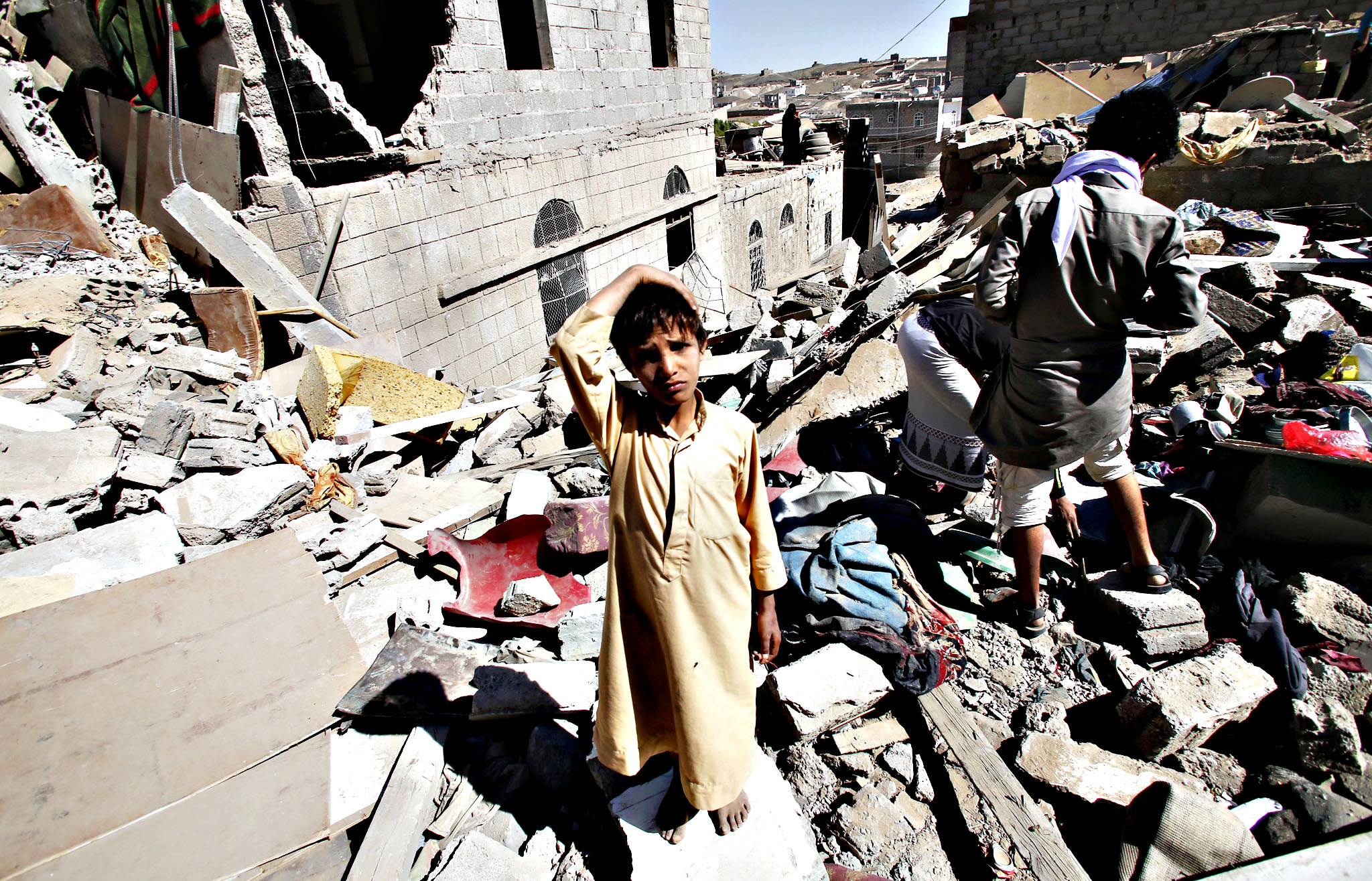 A boy stands in rubble from houses destroyed by Saudi-led airstrikes in Sanaa, Yemen, Friday, May 1, 2015. Saudi Arabia leads a coalition of mostly Sunni Arab countries conducting airstrikes against the rebels who have overrun the Yemeni capital, Sanaa, and forced the Western-backed president, Abed Rabbo Mansour Hadi, to flee the country
