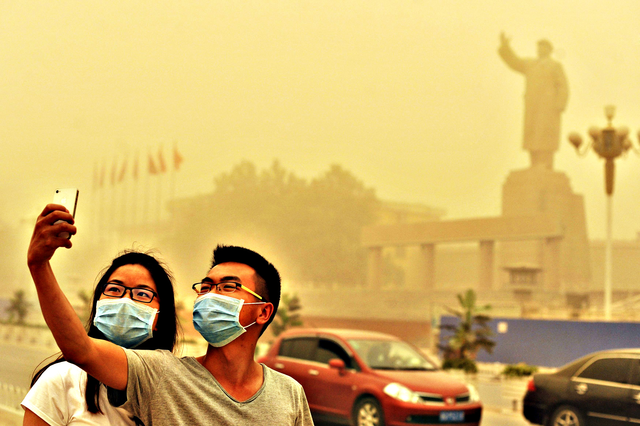 Residents wearing masks pose for a photograph near a statue of late Chinese Chairman Mao Zedong, as a sandstorm hits Kashgar, Xinjiang Uighur Autonomous Region, China