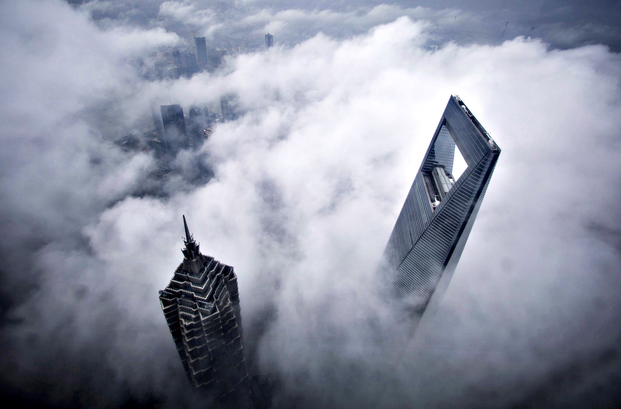 Skyscrapers Shanghai World Financial Center and Jin Mao Tower are seen during heavy rain at the financial district of Pudong in Shanghai on Friday