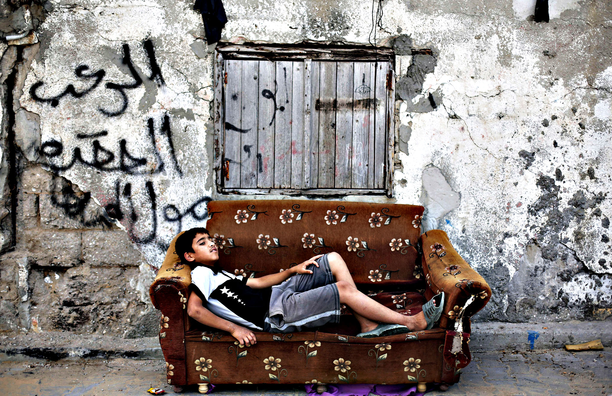A Palestinian boy rests on an old armcha...A Palestinian boy rests on an old armchair in front of a dilapidated house on May 22, 2015 in Gaza City