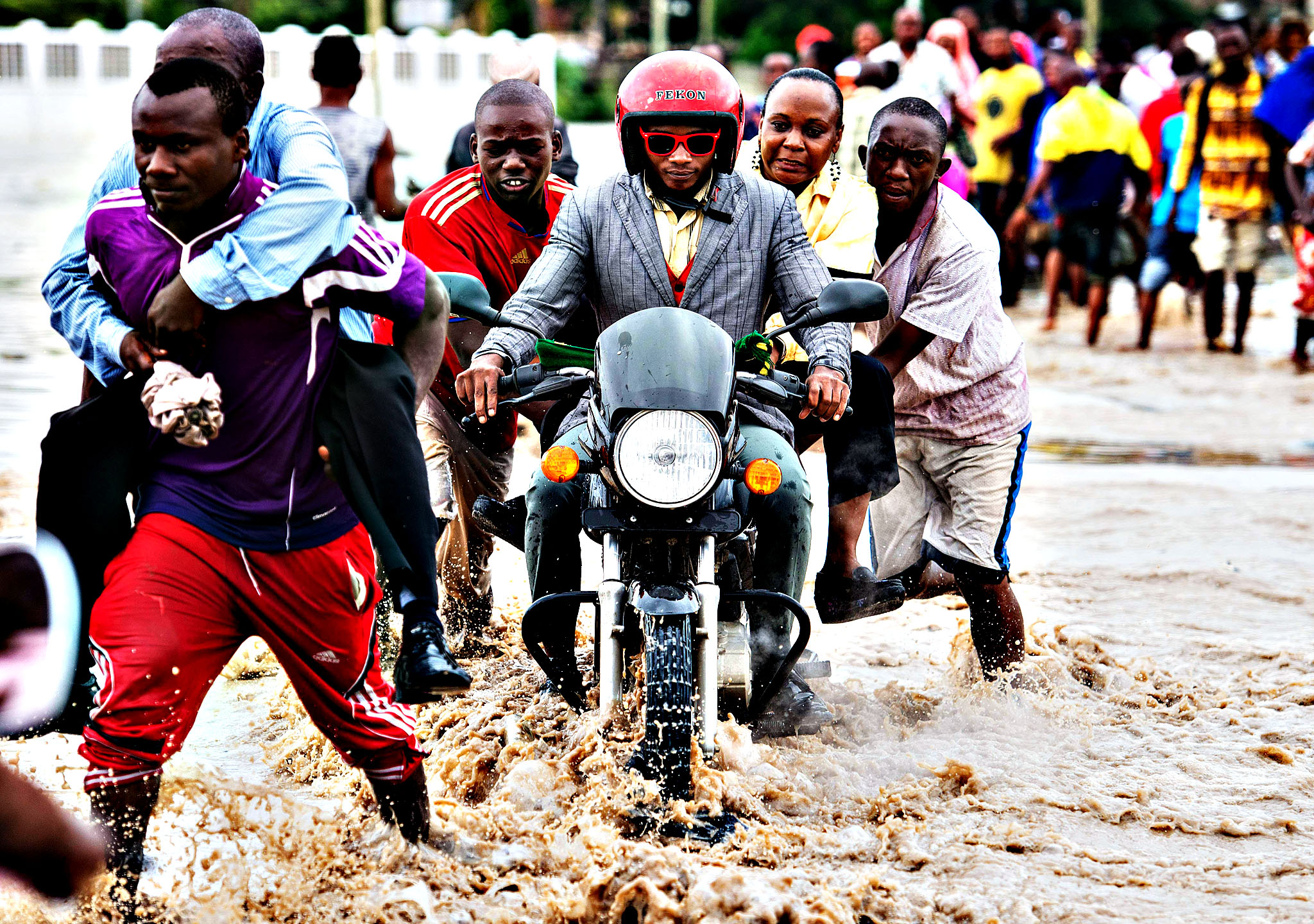 Pedestrians pay for piggy-back rides across flooded Morogoro Road in Dar es Salaam, Tanzania, on Thursday