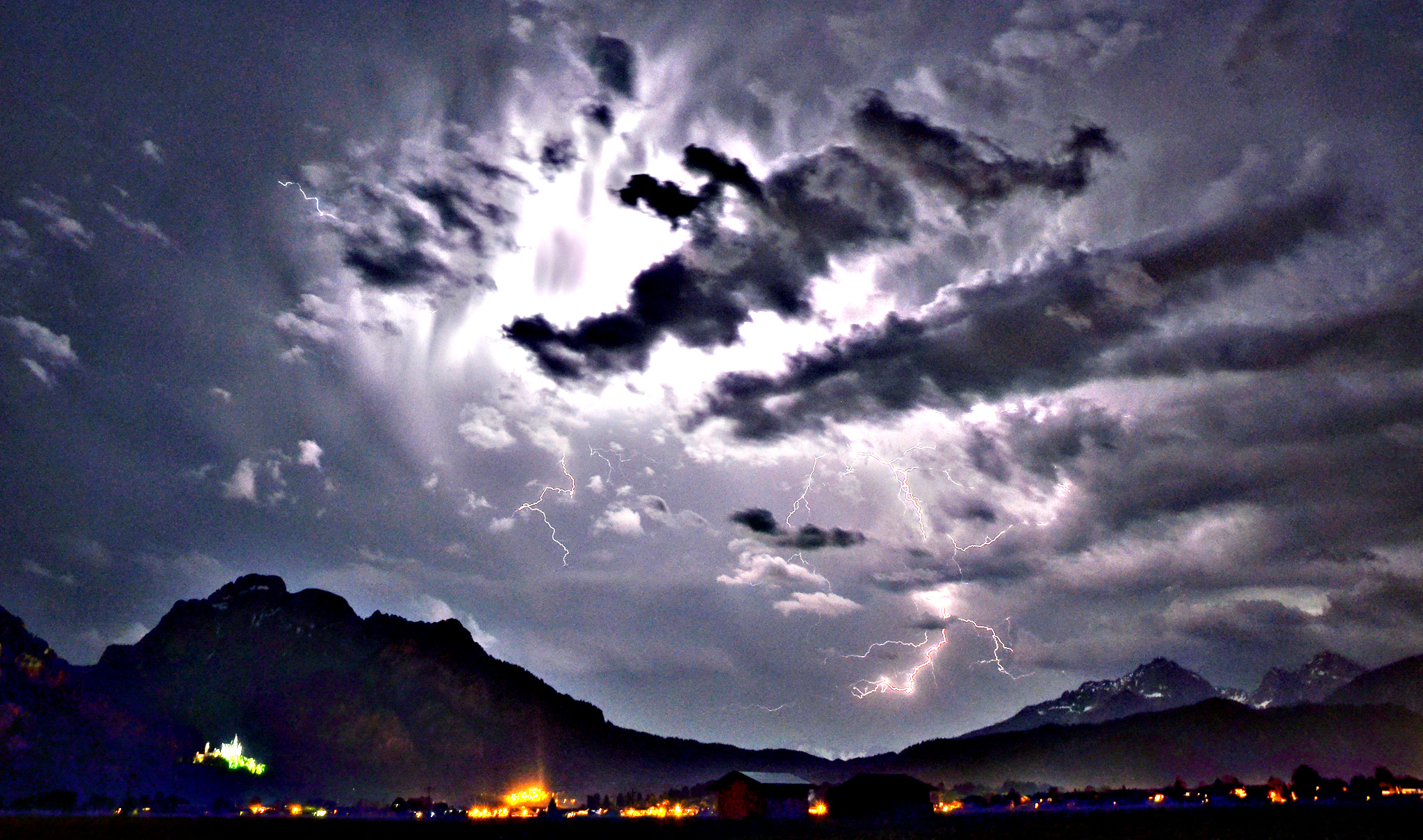 The evening sky in Schwangau, southern Germany, is illuminated by lightning during thunderstorms