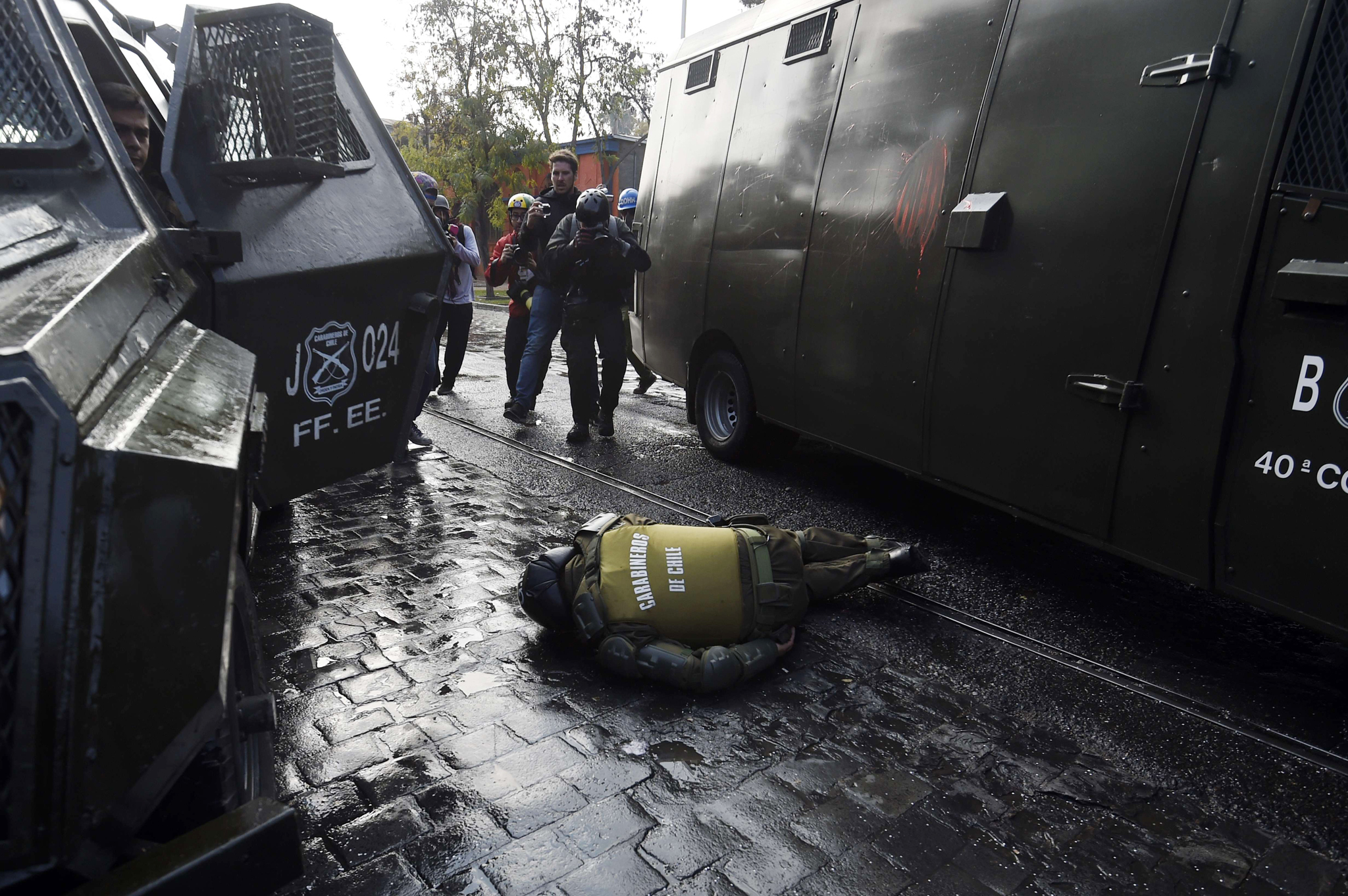 An injured police officer lies ...TOPSHOTS An injured police officer lies on the ground during clashes with violent demonstrators which erupted at the end of a march of students and teachers protesting against what they call inadequate education reforms, in Santiago, on June 10, 2015 on the eve of the start of the 2015 Copa America continental football tournament here in Chile. Thousands of demonstrators took to the streets of Santiago to condemn President Michelle Bachelet's reforms, claiming they fall short of overhauling an unequal education system inherited from the 1973-1990 dictatorship of late ruler Augusto Pinochet.   AFP PHOTO / JUAN BARRETOJUAN BARRETO/AFP/Getty Images