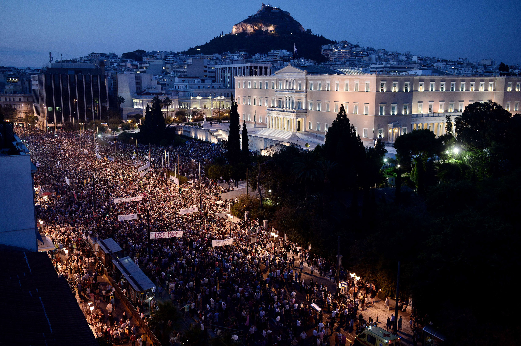 "TOPSHOTS Carrying banners calling for a ""NO"" vote in the forthcoming referendum on bailout conditions set by the country's creditors, protesters gather in front of the Greek parliament in Athens, on june 29, 2015.  Some 17,000 people took to the streets of Athens and Thessalonique to say 'No' to the latest offer of a bailout deal Monday, accusing Greece's international creditors of blackmail. AFP PHOTO / LOUISA GOULIAMAKILOUISA GOULIAMAKI/AFP/Getty Images"