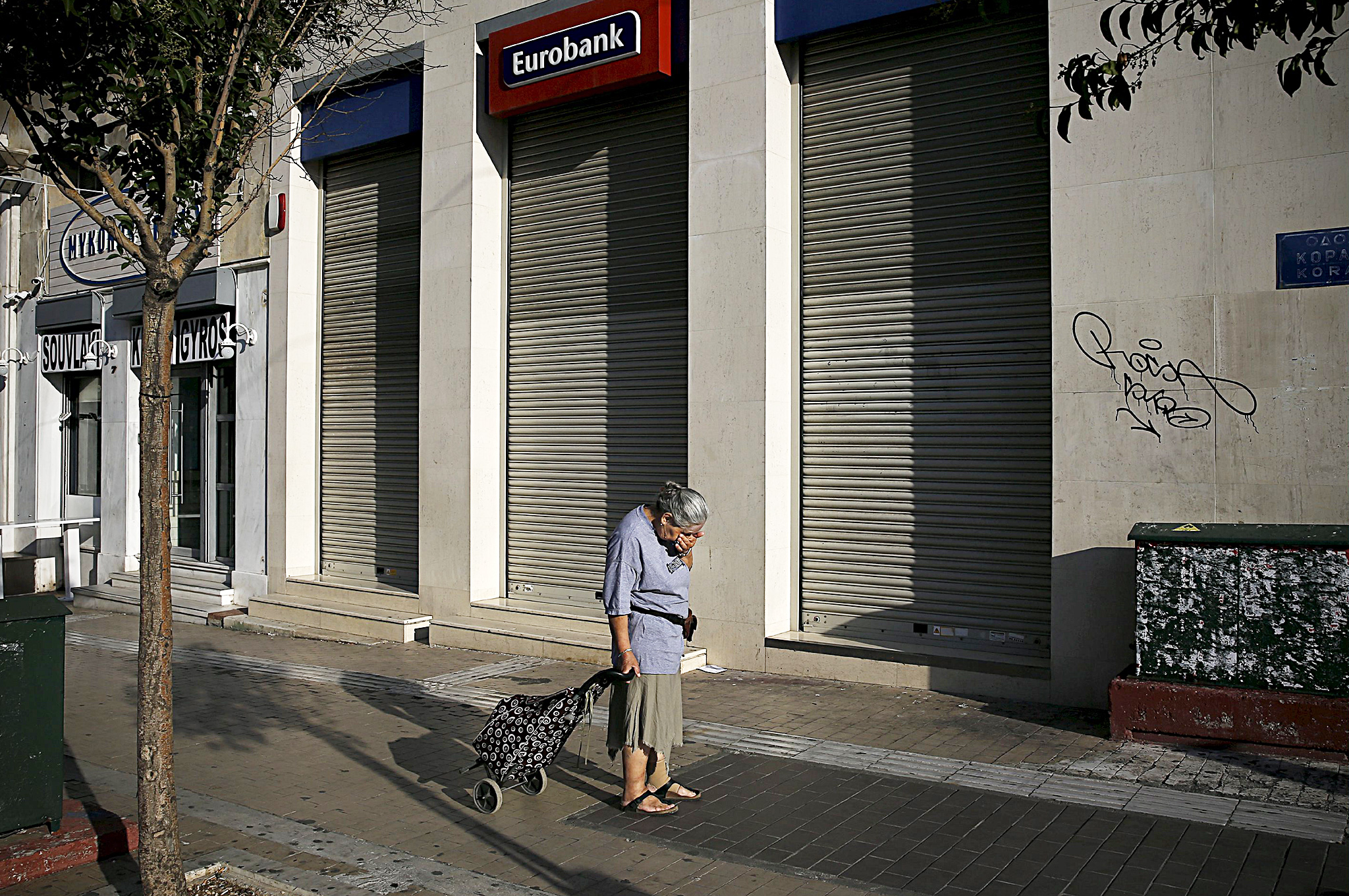 "A woman pulling a shopping cart reacts outside a closed Eurobank branch in Athens...ATTENTION EDITORS - REUTERS PICTURE HIGHLIGHT A woman pulling a shopping cart reacts outside a closed Eurobank branch in Athens, Greece June 29, 2015. Greece closed its banks and imposed capital controls on Sunday to check the growing strains on its crippled financial system, bringing the prospect of being forced out of the euro into plain sight.   REUTERS/Alkis Konstantinidis      TPX IMAGES OF THE DAY REUTERS NEWS PICTURES HAS NOW MADE IT EASIER TO FIND THE BEST PHOTOS FROM THE MOST IMPORTANT STORIES AND TOP STANDALONES EACH DAY. Search for ""TPX"" in the IPTC Supplemental Category field or ""IMAGES OF THE DAY"" in the Caption field and you will find a selection of 80-100 of our daily Top Pictures. REUTERS NEWS PICTURES.  TEMPLATE OUT"