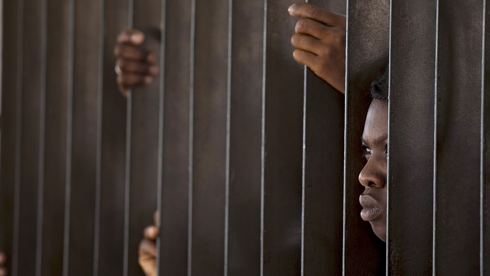 "A Haitian woman peeks through a fence surrounding the Ministry of Interior and Police while waiting to register in Santo Domingo...A Haitian woman peeks through a fence surrounding the Ministry of Interior and Police while waiting to register in Santo Domingo, June 16, 2015. The deadline expires Wednesday night for tens of thousands of undocumented Haitians born in the Dominican Republic under a controversial new immigration law that has aroused international concern from the United Nations and human rights groups. Dominican officials have said those who fail to registar under a ""Regularization Plan"" will be deported within 45 days. REUTERS/Ricardo Rojas        TPX IMAGES OF THE DAY"