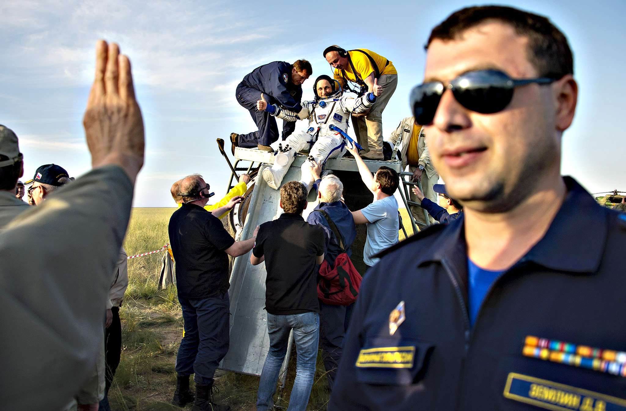 "Ground personnel help International Space Station (ISS) rew member Anton Shkaplerov of Russia out of the Soyuz TMA-15M shortly after landing near the town of Zhezkazgan, Kazakhstan, June 11, 2015. Three astronauts landed safely in the steppes of Kazakhstan on Thursday, ending their 199-day mission after an unexpected ""bonus month"" aboard the International Space Station, NASA Television showed"