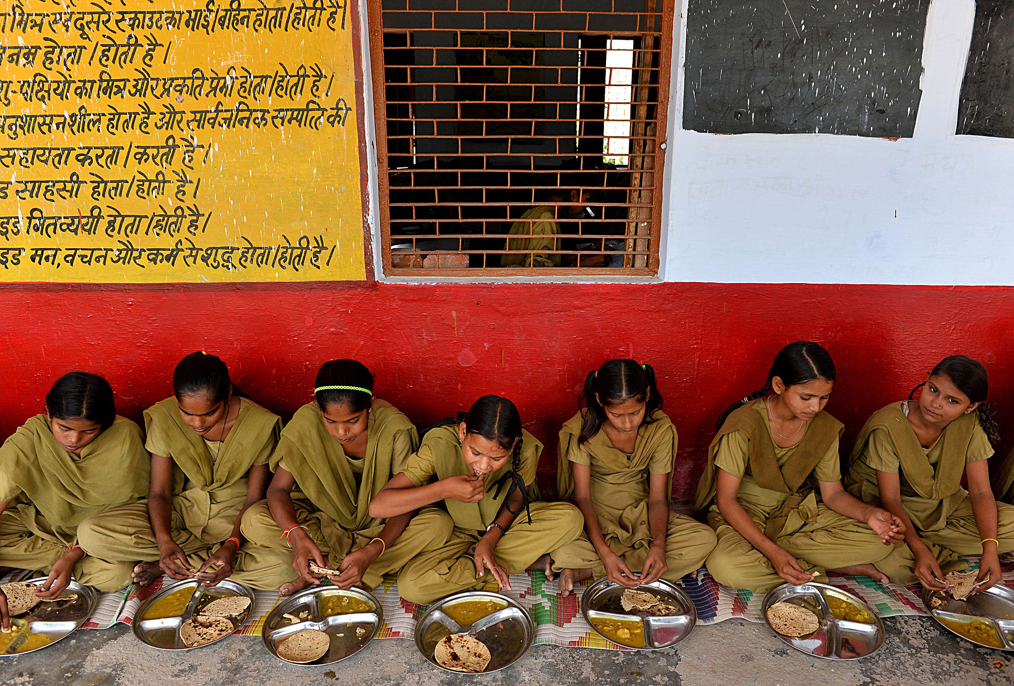 TO GO WITH India-education-school-health...TO GO WITH India-education-school-health-food,FEATURE by Abhaya SRIVASTAVA In this photo taken on May 19, 2015, Indian schoolgirls eat lunch organised by the non-profit Akshaya Patra Foundation, at the Chaumuha Primary School on the outskirts of Vrindavan.  Churning out 1.2 tonnes of curry in under an hour, women stirring vats in the spotlessly clean, high-tech kitchen are hoping to erase the shocking reputation of India's free school lunch scheme.    AFP PHOTO / Chandan KHANNAChandan Khanna/AFP/Getty Images