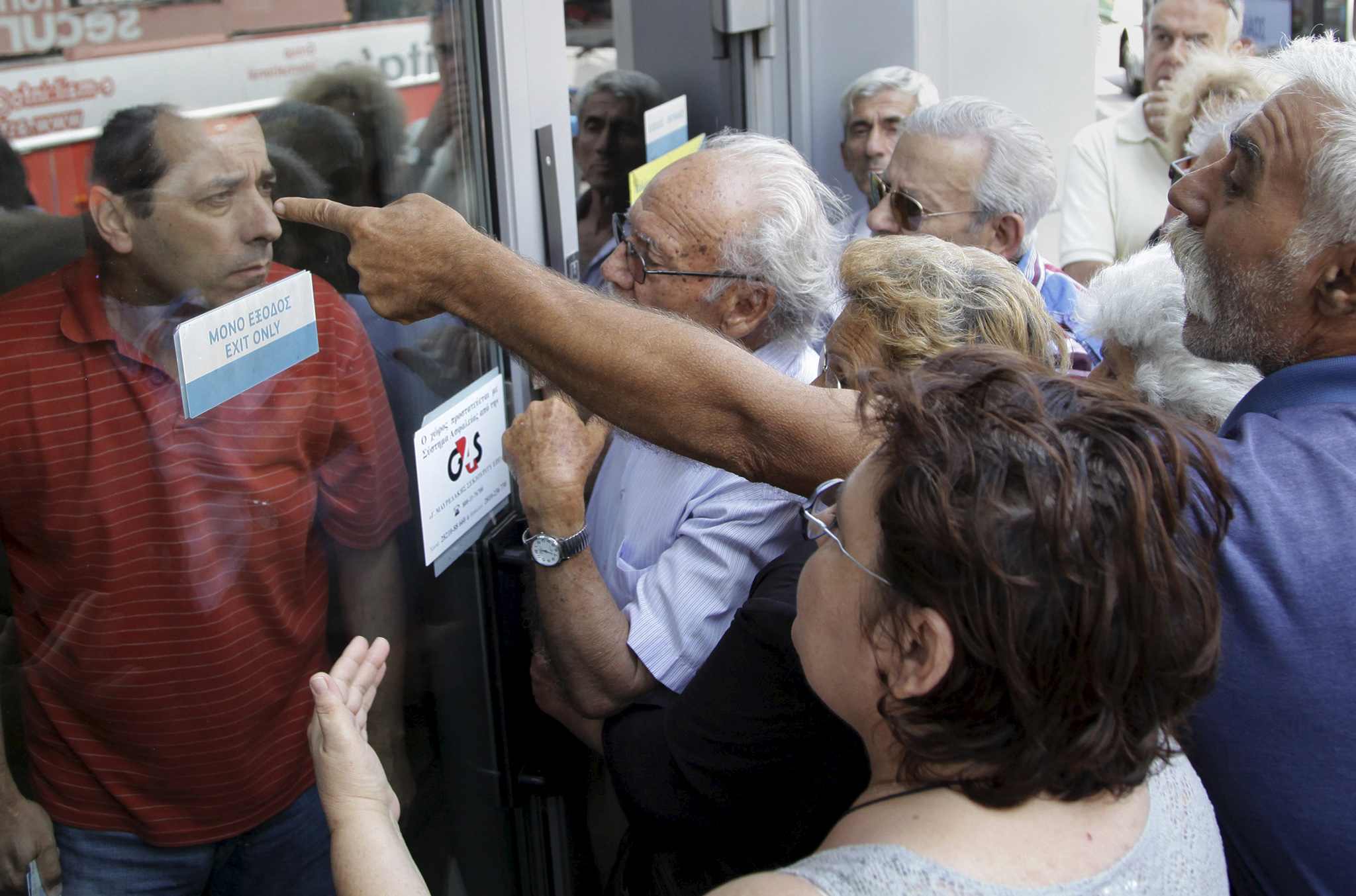 Pensioners waiting outside a closed National Bank branch and hoping to get their pensions, argue with a bank employee through a closed door in Iraklio on the island of Crete.