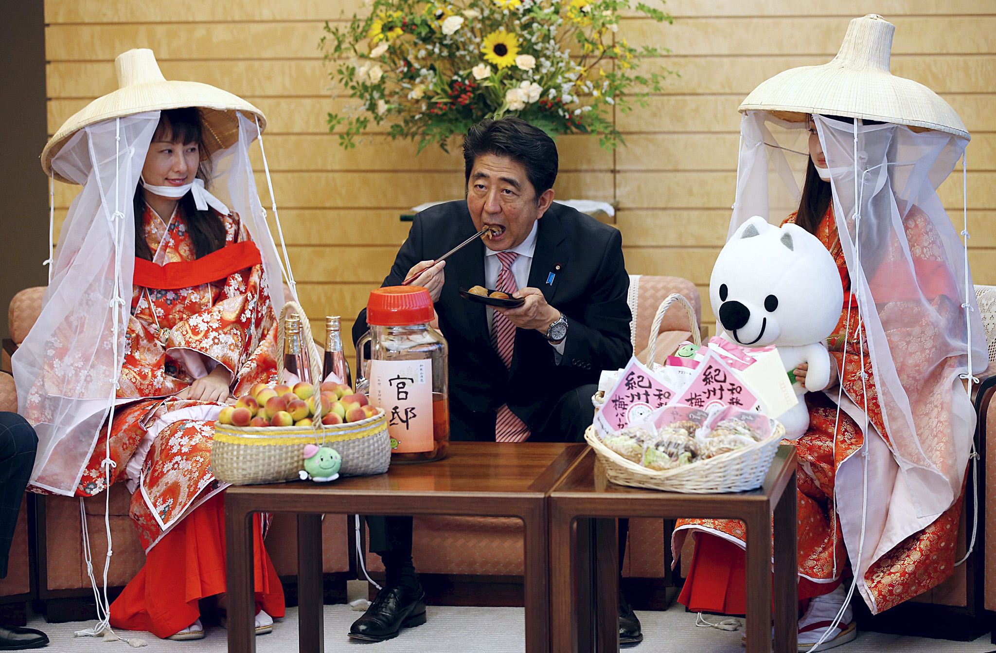 Japan's PM Abe eats a pickled plum as he meets with Miss Plum Baba and Kimoto, who are representing the Kishu Plum Organization, at Abe's official residence in Tokyo...Japan's Prime Minister Shinzo Abe (C) eats a pickled plum as he meets with Miss Plum Fuyuka Baba (R) and Miss Plum Kozue Kimoto, who are representing the Kishu Plum Organization, at Abe's official residence in Tokyo June 5, 2015.    REUTERS/Toru Hanai