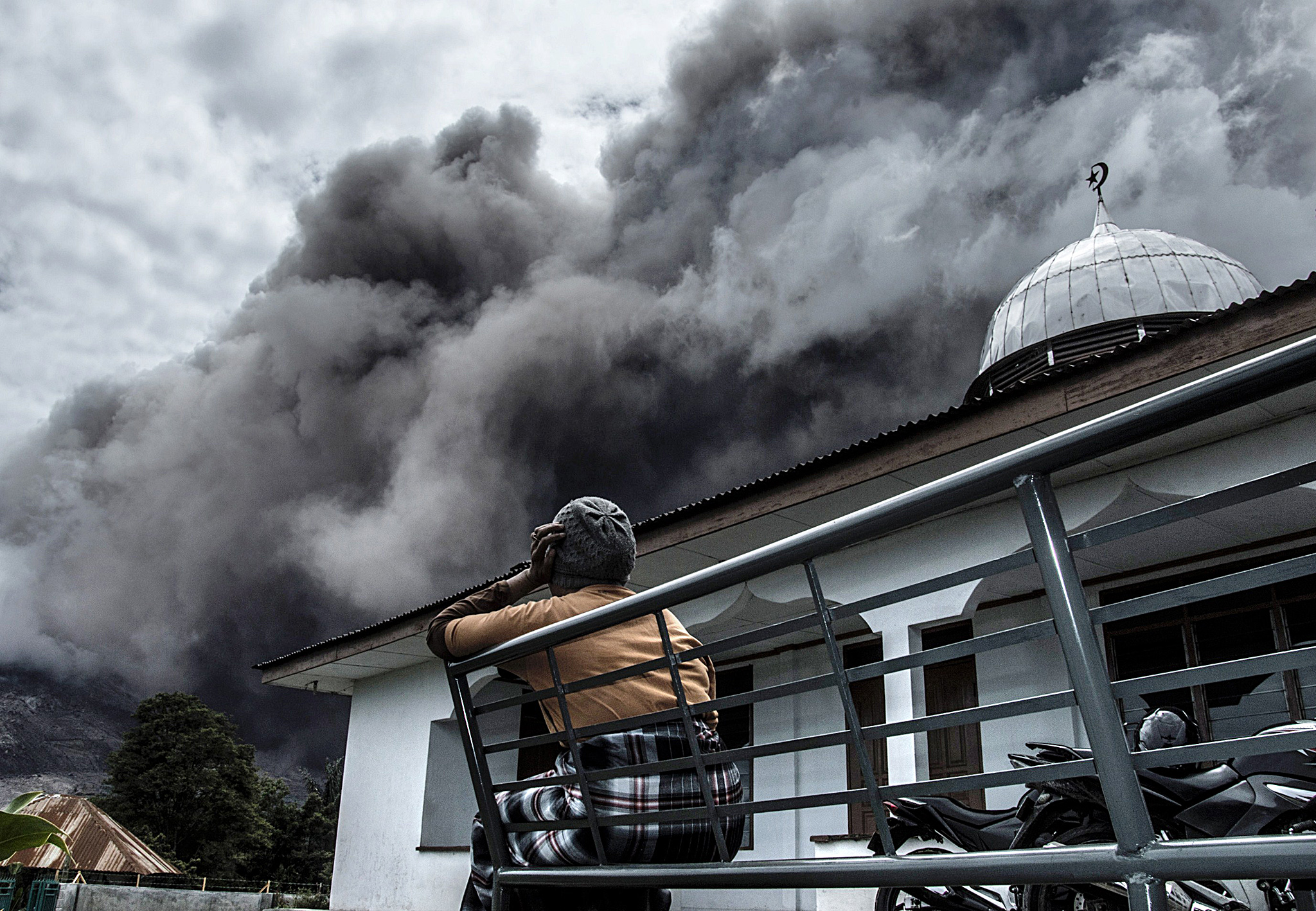 An Indonesian woman looks on as the Moun...An Indonesian woman looks on as the Mount Sinabung volcano spews ash as seen from the nearest village in Karo district, North Sumatra province, on June 16, 2015. More than 1,200 Indonesian villagers were evacuated June 15 from their homes close to a rumbling volcano on Sumatra island, an official said. AFP PHOTO / Sutanta ADITYASUTANTA ADITYA/AFP/Getty Images