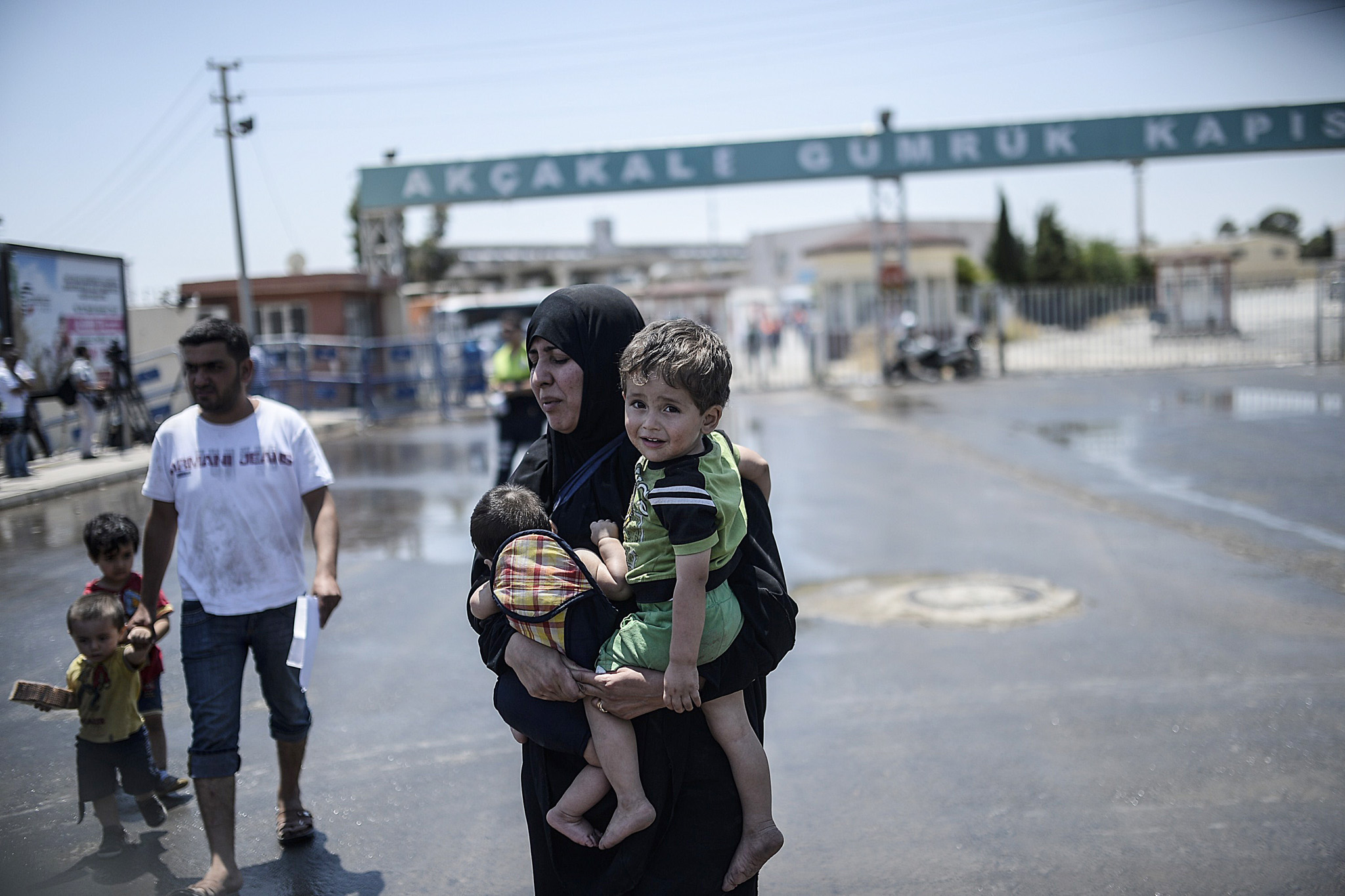 "A Syrian woman fleeing the war walks wit...A Syrian woman fleeing the war walks with her children after crossing into Turkey at the Akcakale border crossing, in Sanliurfa province on June 15, 2015. Turkey said it was taking measures to limit the flow of Syrian refugees onto its territory after an influx of thousands more over the last days due to fighting between Kurds and jihadists. Under an ""open-door"" policy, Turkey has taken in 1.8 million Syrian refugees since the conflict in Syria erupted in 2011. AFP PHOTO / BULENT KILICBULENT KILIC/AFP/Getty Images"