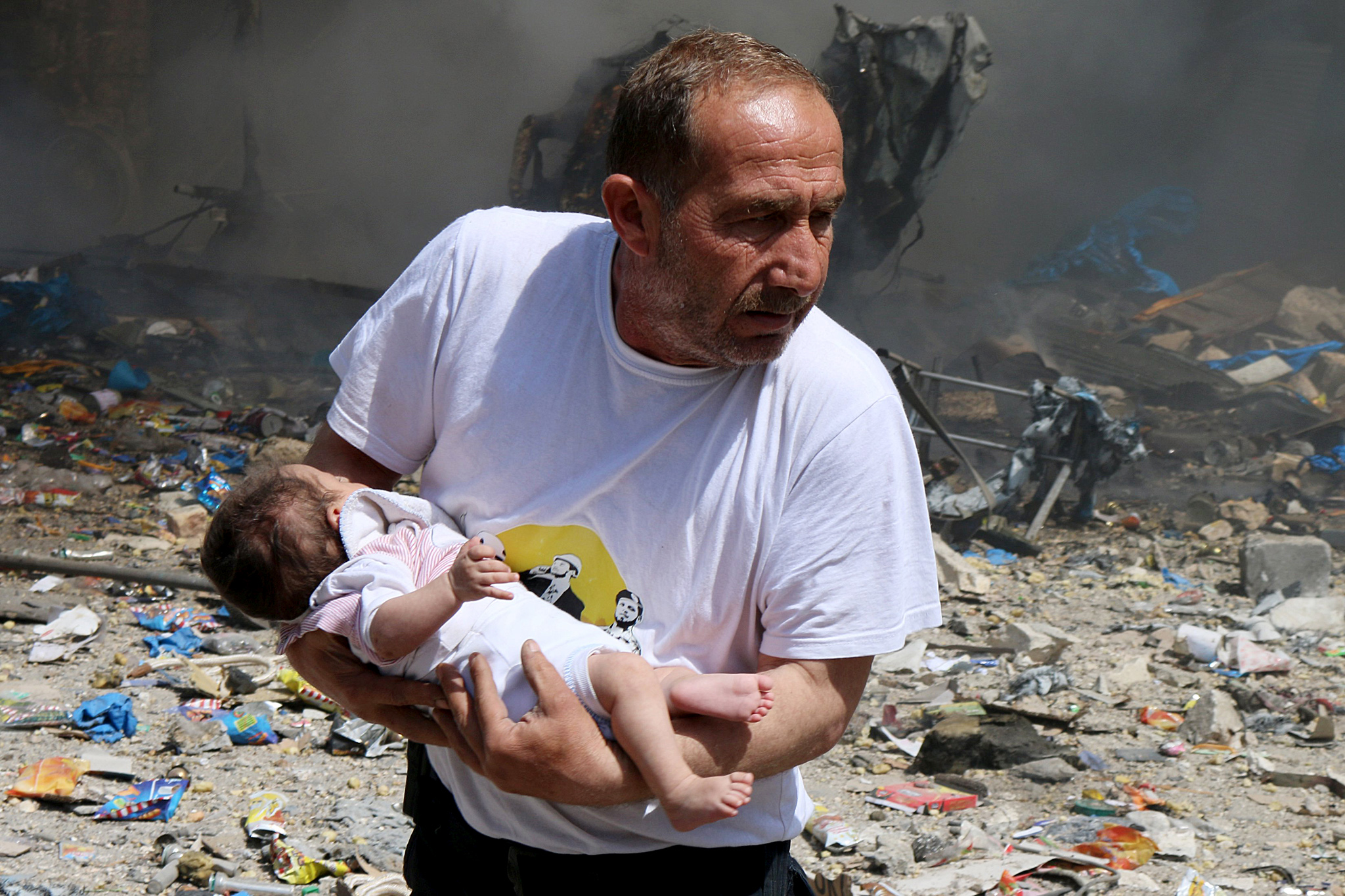 A man holds a baby that survived what activists said was a site hit by a barrel bomb dropped by forces loyal to Syrian President Bashar al-Assad at the old city of Aleppo...A man holds a baby that survived what activists said was a site hit by a barrel bomb dropped by forces loyal to Syrian President Bashar al-Assad at the old city of Aleppo June 3, 2015. REUTERS/Abdalrhman Ismail
