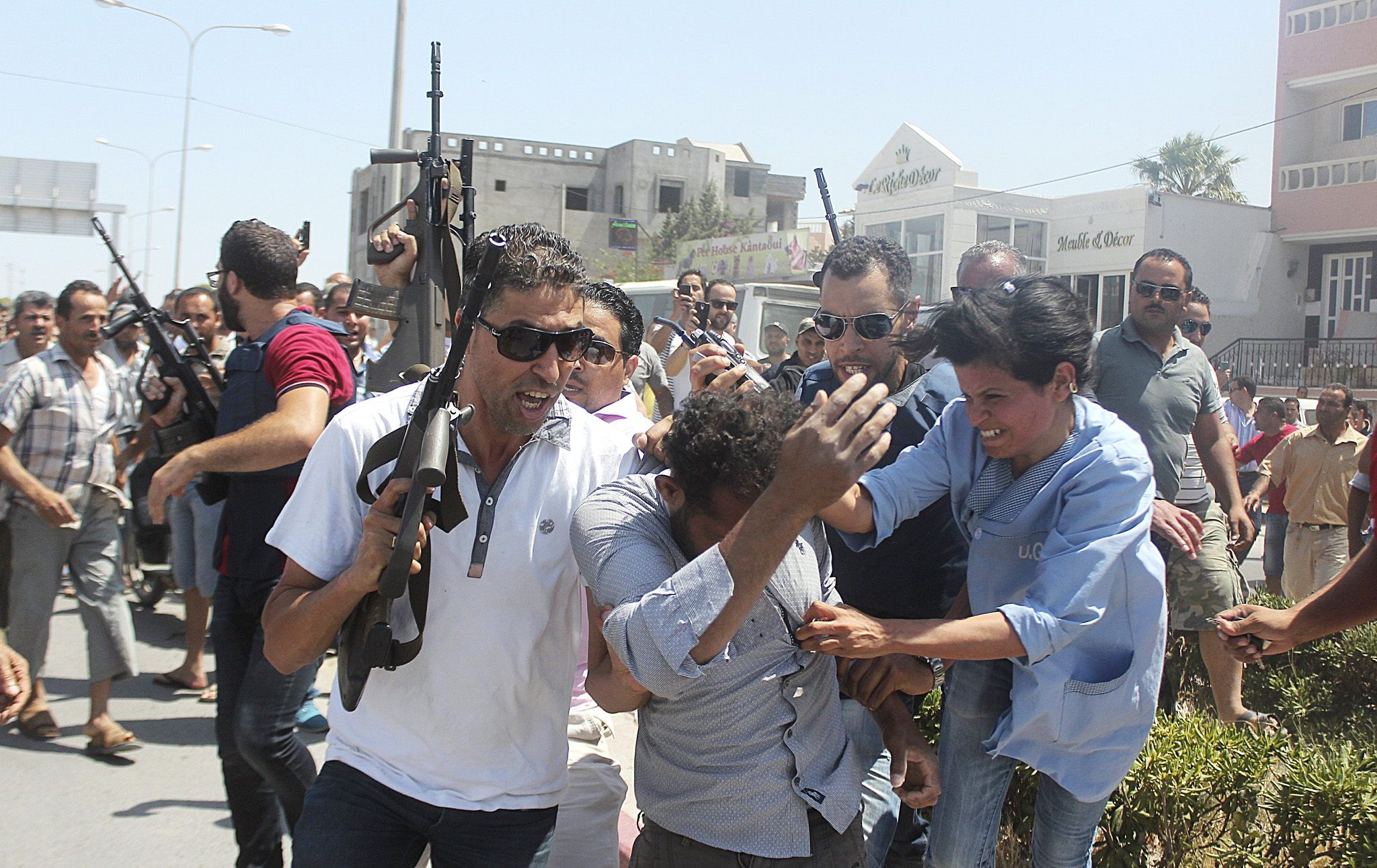Police officers control the crowd while surrounding a man suspected to be involved in opening fire on a beachside hotel in Sousse...Police officers control the crowd (rear) while surrounding a man (front C) suspected to be involved in opening fire on a beachside hotel in Sousse, Tunisia, as a woman reacts(R), June 26, 2015. At least 27 people, including foreign tourists, were killed when at least one gunman opened fire on a Tunisian beachside hotel in the popular resort of Sousse on Friday, an interior ministry spokesman said. Police were still clearing the area around the Imperial Marhaba hotel and the body of one gunman lay at the scene with a Kalashnikov assault rifle after he was shot in an exchange of gunfire, a security source at the scene said. REUTERS/Amine Ben Aziza   TPX IMAGES OF THE DAY