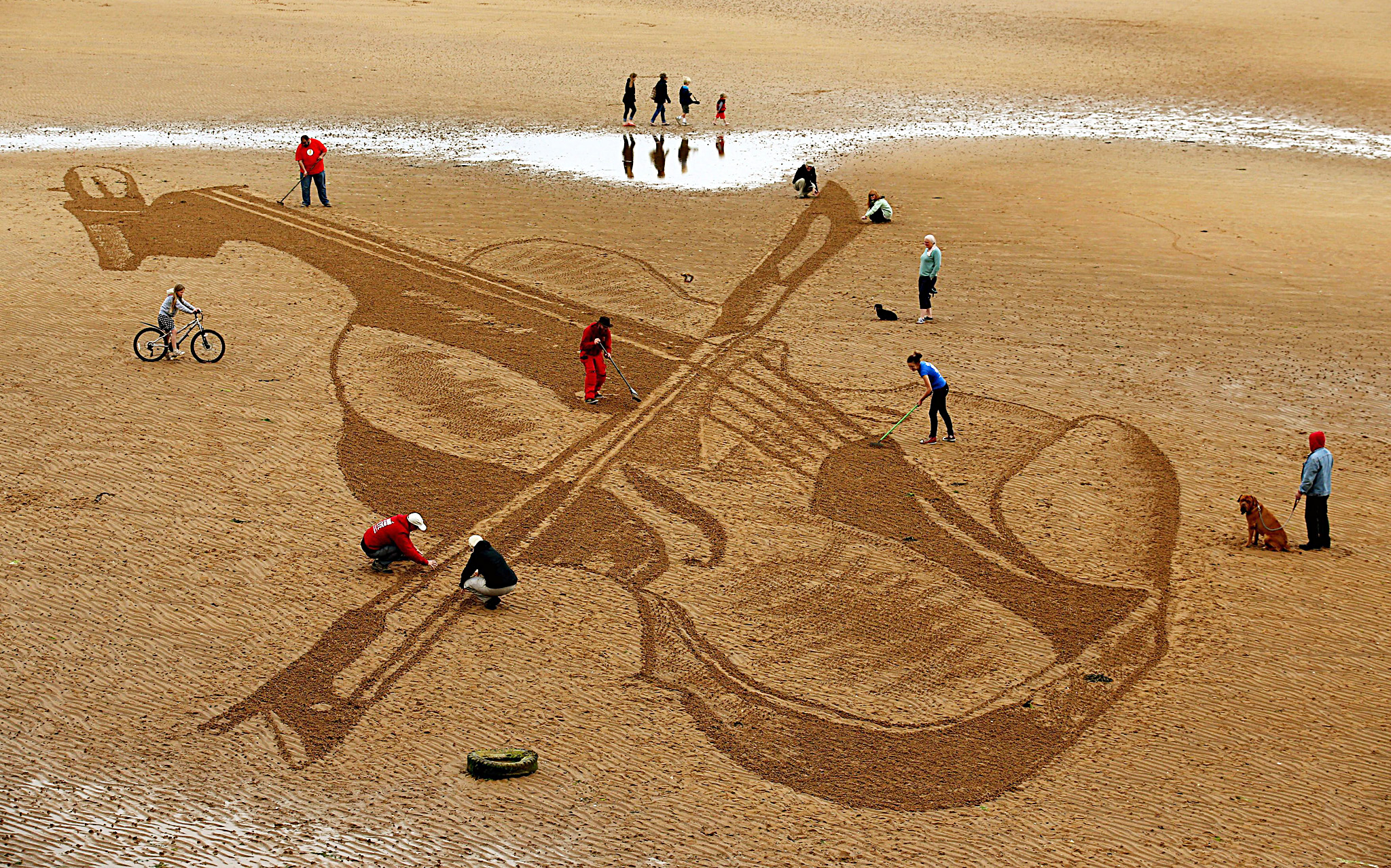 Sand art in Elie...People watch as Jamie Wardley (centre left) and Claire Jamieson (centre right) who are part of the Sand in Your Eye team, draw a violin on Elie Beach in Fife in honour of a 300 year old Stradivarius violin which is on loan to the 2015 East Neuk Festival. PRESS ASSOCIATION Photo. Picture date: Monday June 29, 2015. The drawing has been created using sticks and rakes. Photo credit should read: Andrew Milligan/PA Wire