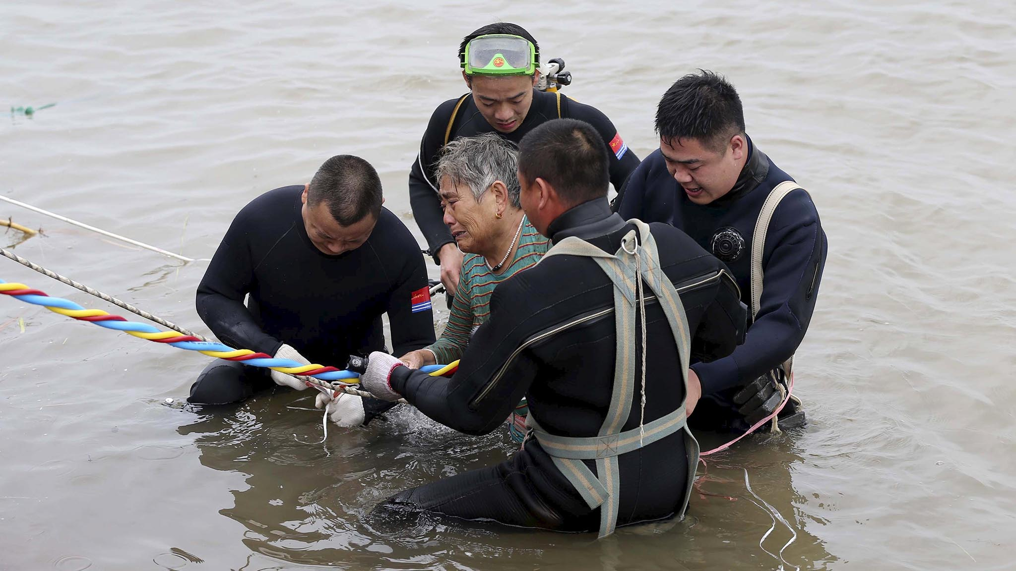 A woman is helped after being pulled out by divers from a sunken ship in Jianli