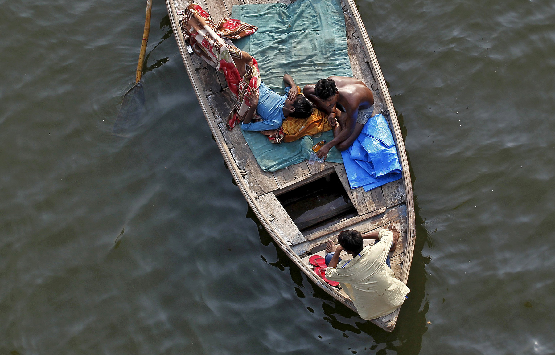 Fishermen rest on a boat after fishing in the waters of river Yamuna during early morning in Allahabad