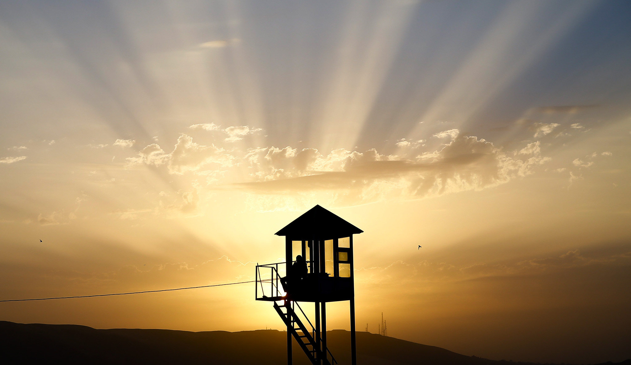 A police watch tower is silhoutted during sunset in Baku, Azerbaijan.