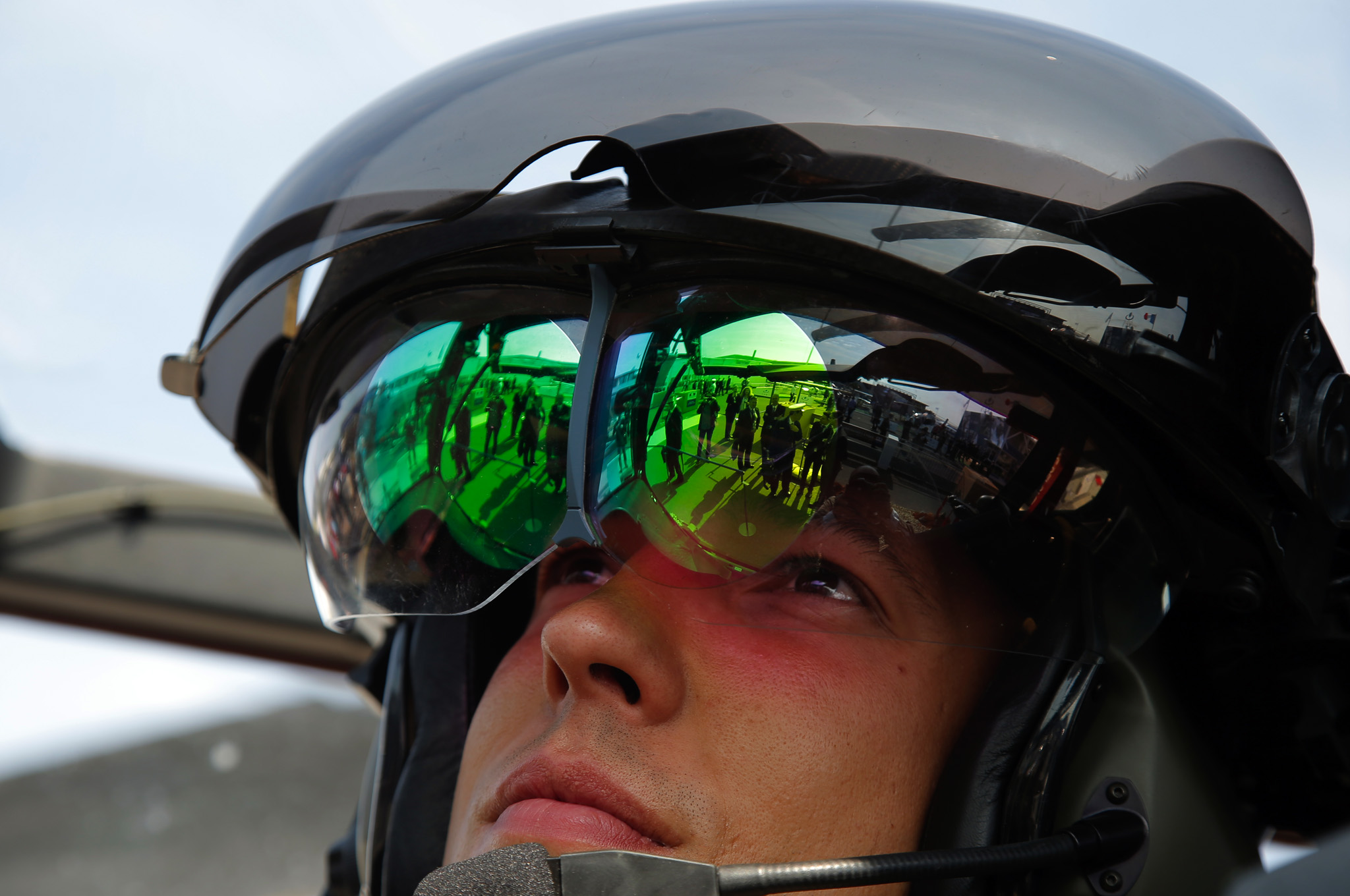 Visitiors to the  Paris Air Show are reflected in the helmet visor worn by French Lieutenant Romain of the 1st Combat Helicopter Regiment.