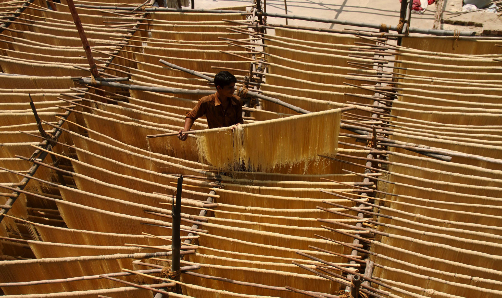 A worker prepares vermicelli at a workshop in Hyderabad, Pakistan, ahead of the holy fasting month of Ramadan.