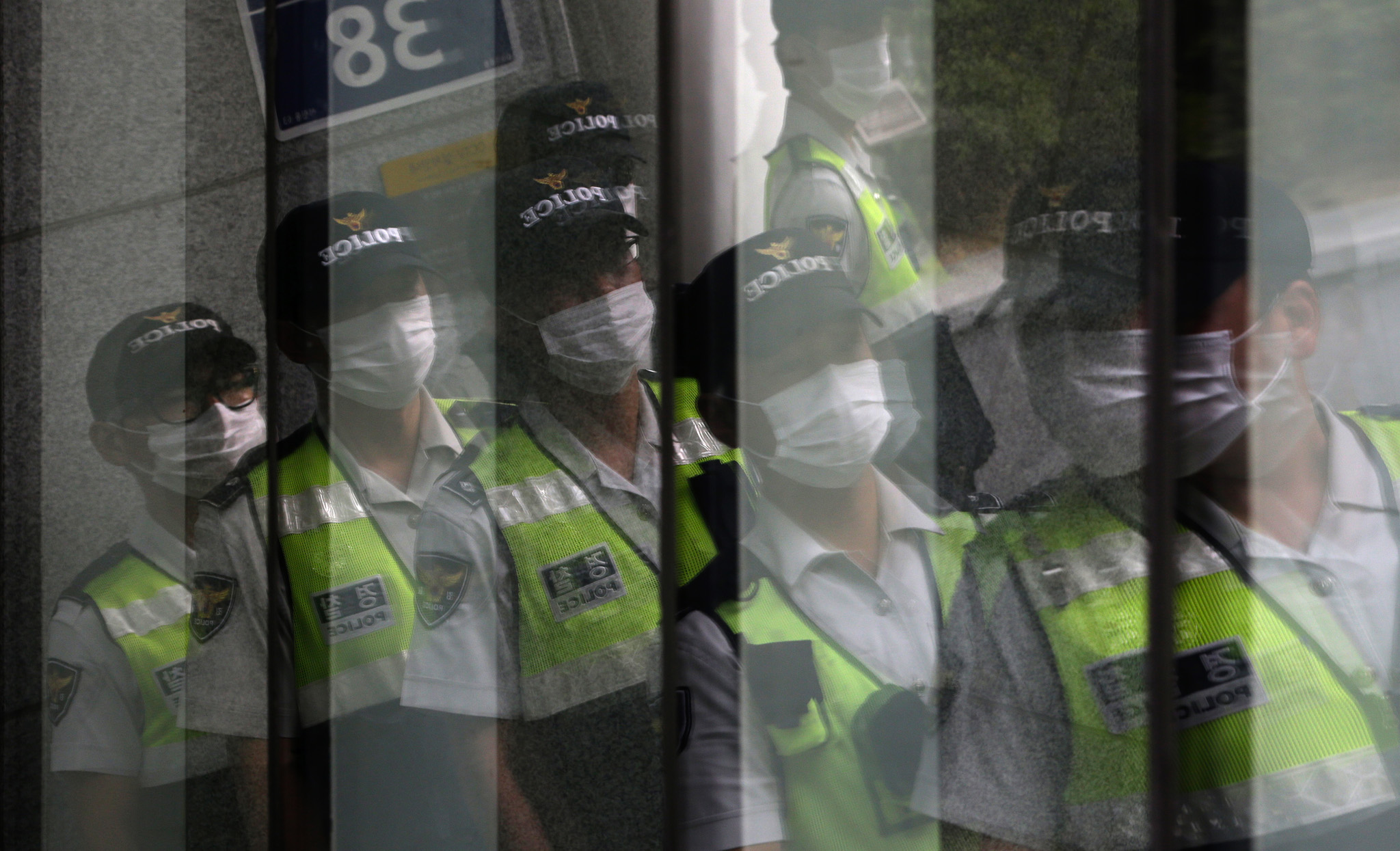 Police officers wearing masks as a precaution against Middle East Respiratory Syndrome (MERS) are reflected on windows in Seoul, South Korea.