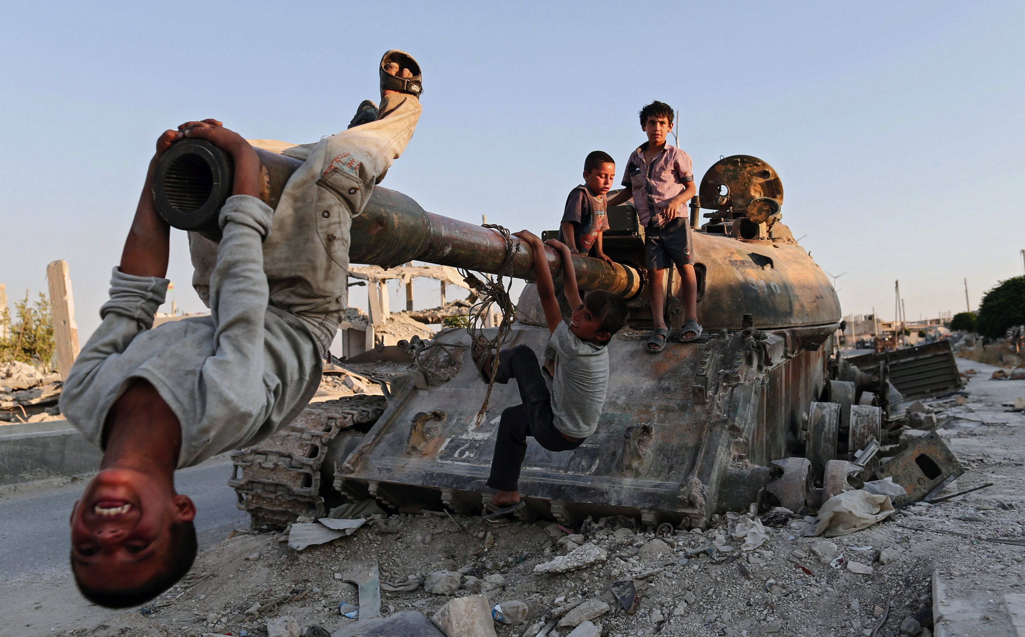 Syrian children play on a destroyed tank in south of Kobane in Syria.