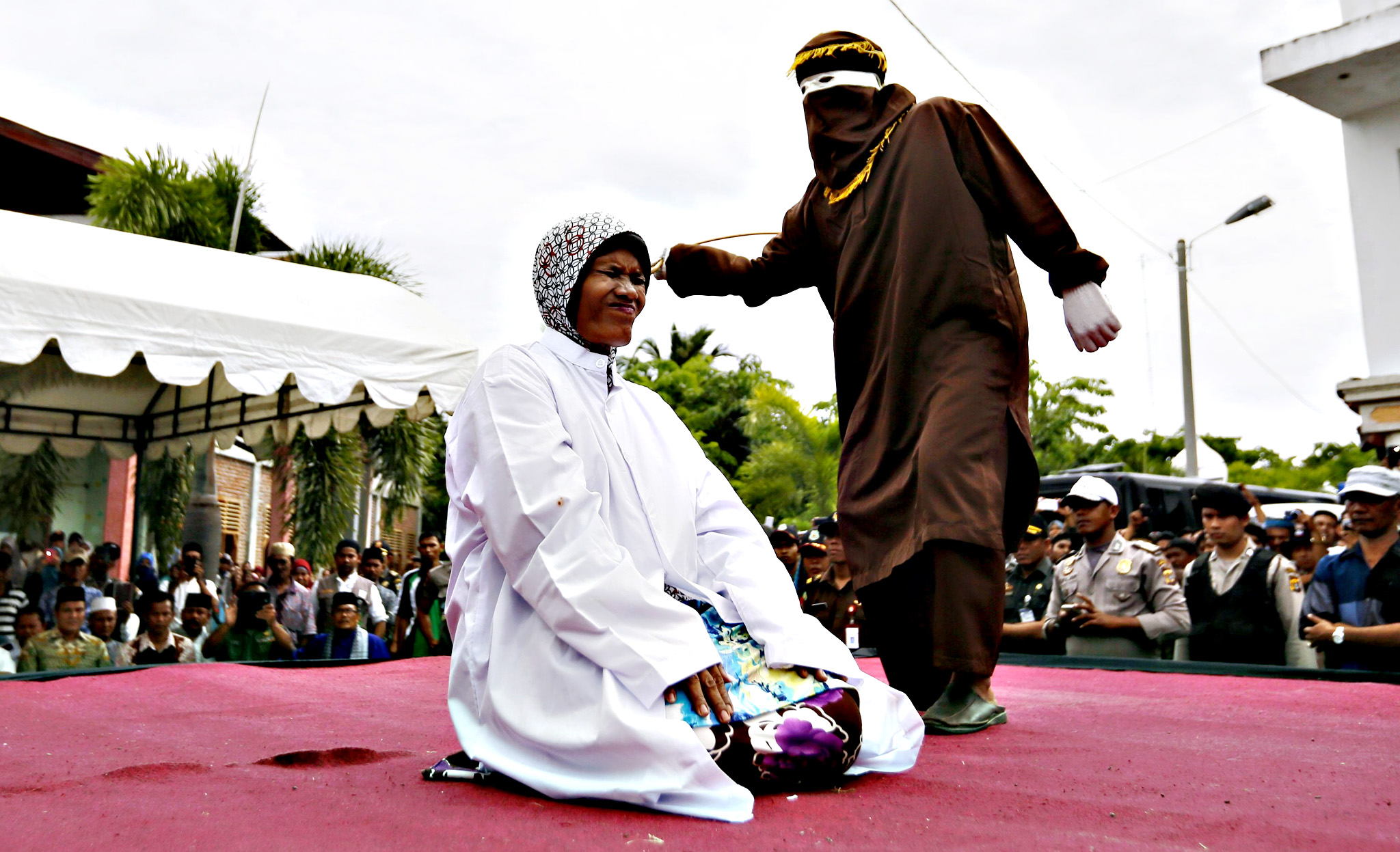 An Acehnese woman reacts as she is publicly whipped with a cane as punishment, in Banda Aceh, Aceh, Indonesia, Friday. Four women and three men were caned by Sharia police in Aceh for having sex affairs without being married