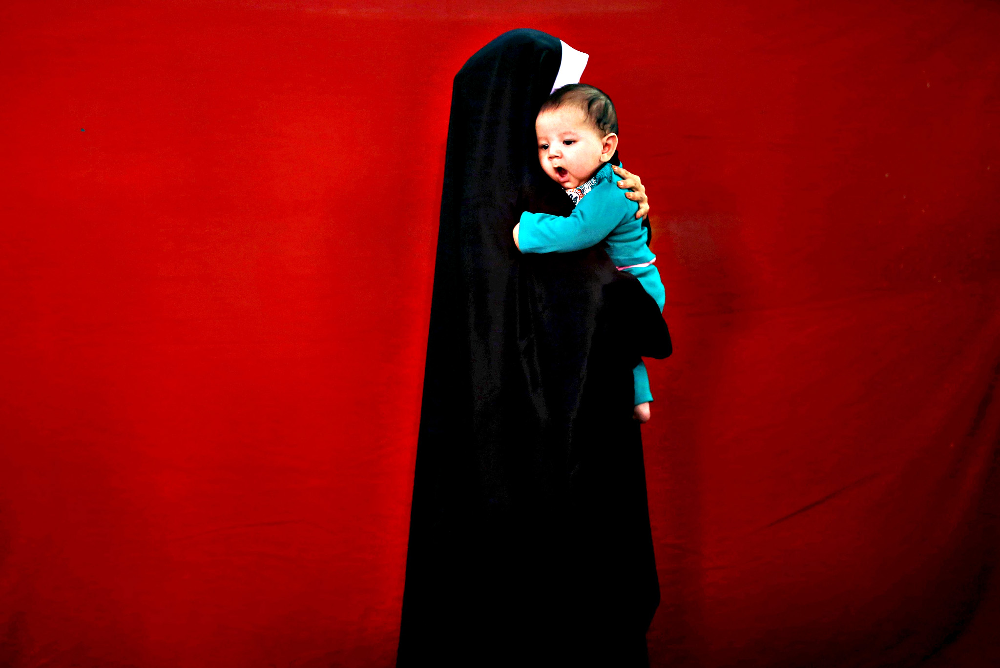 "An Afghan woman holds her child as she visits the inauguration of ""Spring of Holy Koran"" exhibition during the month of Ramadan, in Kabul, Afghanistan June 25, 2015"