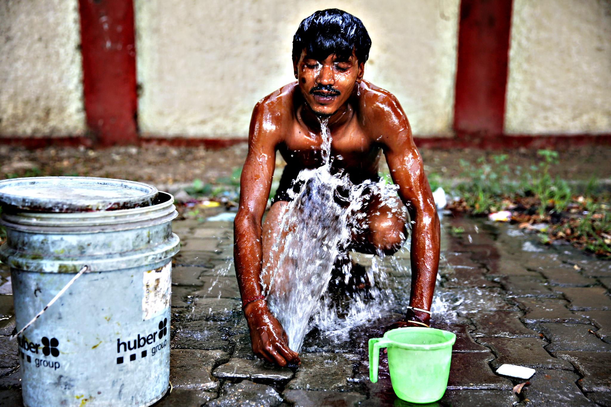 An Indian rickshaw driver takes bath using water from a leaking pipe as it flows through a drain beneath on a hot summer morning in Allahabad, India, Thursday, June 11, 2015. India s northern state of Uttar Pradesh continued to reel under intense condition as heat waves prevailed in several parts of the state with temperatures recording 45 degrees Celsius (113 degrees Fahrenheit)